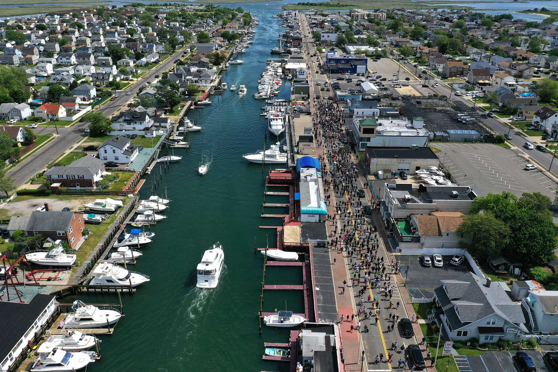 n aerial view of Protesters marching along the Nautical Mile on June 07, 2020 in Freeport, New York.  Minneapolis Police officer Derek Chauvin was filmed kneeling on George Floyd's neck, who was later pronounced dead at a local hospital. Chauvin has been charged with second-degree murder and three other officers who participated in the arrest have been charged with aiding and abetting second-degree murder. Floyd's death, the most recent in a series of deaths of black Americans by the police, has set off days and nights of protests across the country.