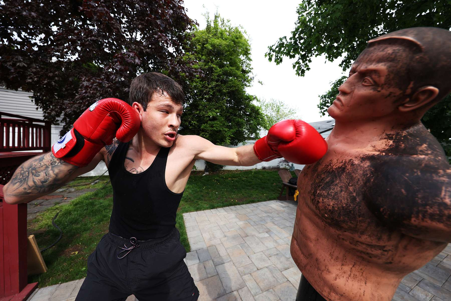 Zach Blumberg punches a boxing dummy he has named Bob in his backyard on May 18, 2020 in Oceanside, New York.  Zach is an Amateur boxer who fought in the New York City Golden Gloves. He was training to compete in this year's Golden Gloves tournament but it has been cancelled due to the coronavirus pandemic.  The Gym he fights for is called the Freeport Boxing Club and has been closed by New York Governor Andrew Cuomo since March 16th due to the coronavirus COVID-19 pandemic.  Until the gyms are deemed safe to open he will continue to stay fit by training at home with the hope that he can box again later this year.