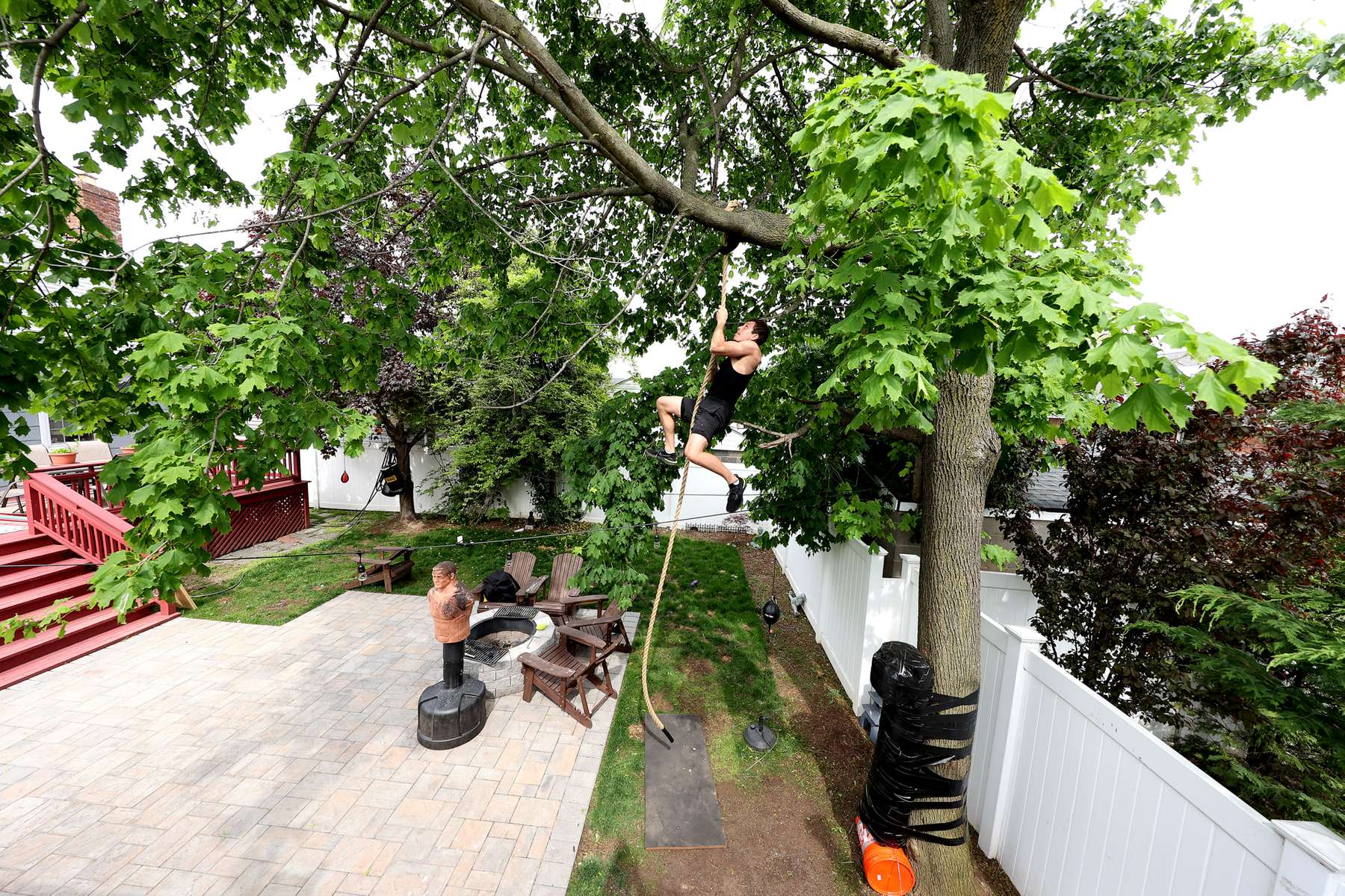Zach Blumberg climbs a rope he attached to the top of a tree in his backyard on May 18, 2020 in Oceanside, New York.  Zach is an Amateur boxer who fought in the New York City Golden Gloves. He was training to compete in this year's Golden Gloves tournament but it has been cancelled due to the coronavirus pandemic.  The Gym he fights for is called the Freeport Boxing Club and has been closed by New York Governor Andrew Cuomo since March 16th due to the coronavirus COVID-19 pandemic.  Until the gyms are deemed safe to open he will continue to stay fit by training at home with the hope that he can box again later this year.