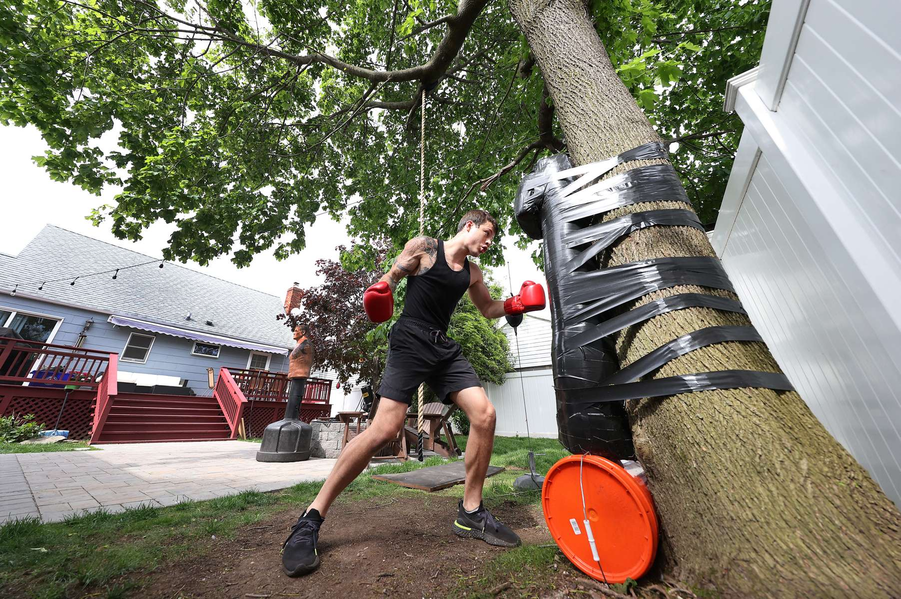 Zach Blumberg punches a homemade heavy bag he attached with duct tape to a tree in his backyard on May 18, 2020 in Oceanside, New York.  Zach is an Amateur boxer who fought in the New York City Golden Gloves. He was training to compete in this year's Golden Gloves tournament but it has been cancelled due to the coronavirus pandemic.  The Gym he fights for is called the Freeport Boxing Club and has been closed by New York Governor Andrew Cuomo since March 16th due to the coronavirus COVID-19 pandemic.  Until the gyms are deemed safe to open he will continue to stay fit by training at home with the hope that he can box again later this year.