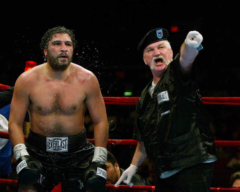 Norman Stone, trainer of Puerto Rico's John Ruiz (black shorts) points to his opponent Fres Oquendo during their World Boxing Association Heavyweight title fight at Madison Square Garden on April 17, 2004 in New York City.  Referee Wayne Kelley halted the fight in the 11th round, and declared John Ruiz the winner.