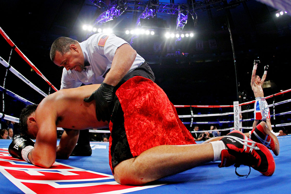 Mike Ruiz of Puerto Rico is checked on by referee Eddie Claudio after getting knocked out by Glen Tapia of the United States during their Super Welterweight fight at Madison Square Garden on December 3, 2011 in New York City.
