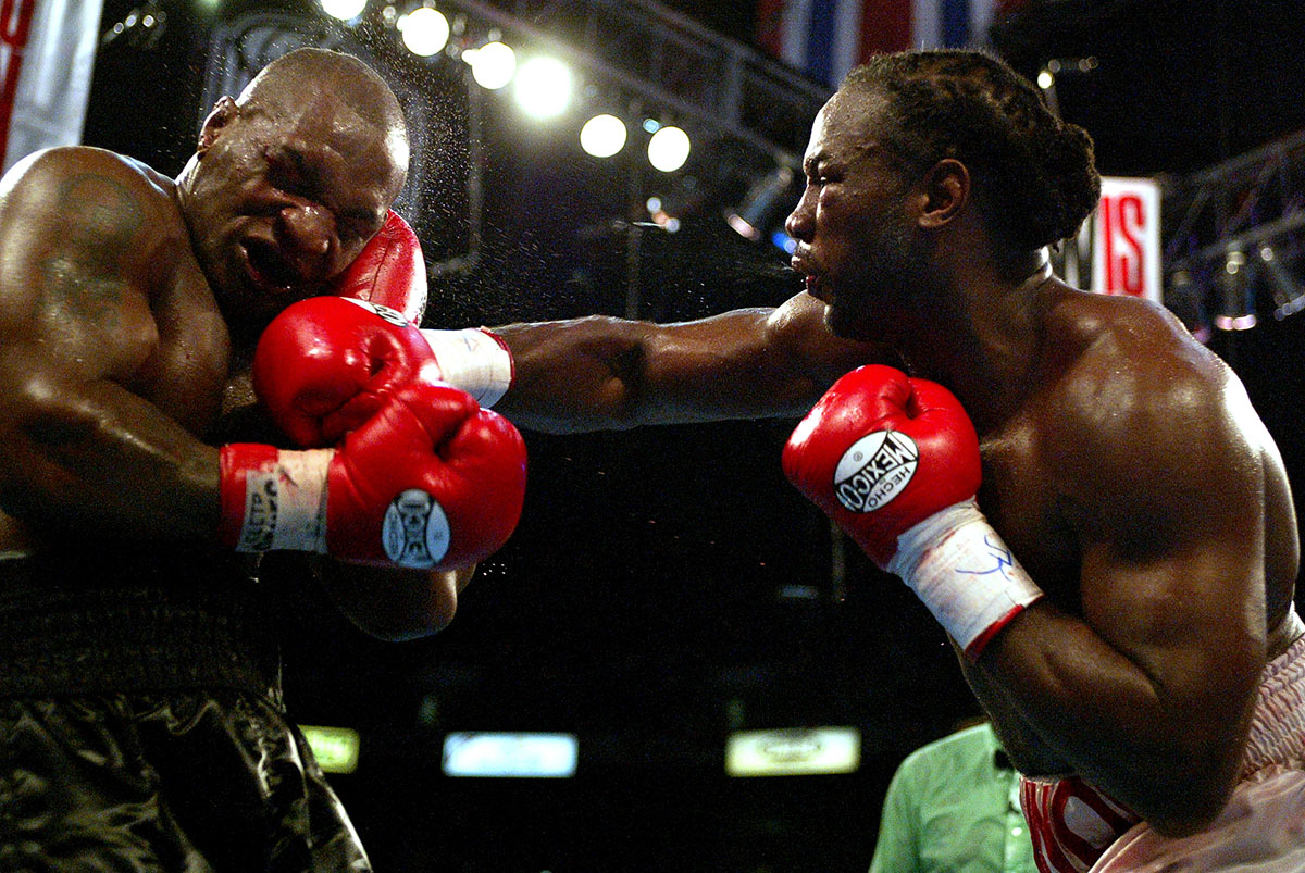 Lennox Lewis hits Mike Tyson with a right hook in the 8th round during their WBC/IBF heavyweight championship bout on June 8, 2002 at The Pyramid in Memphis, Tennessee.