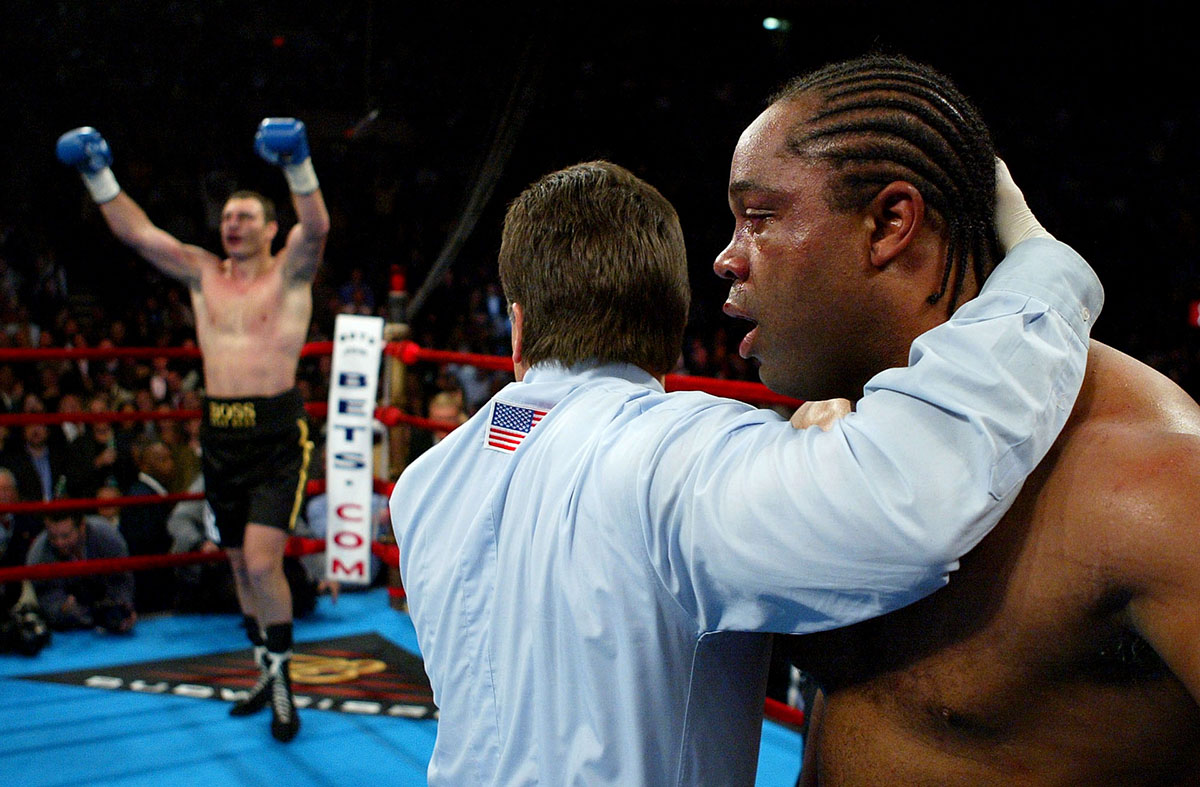 Kirk Johnson is held by referee Aurthur Mercante Jr. as Vitali Klitschko celebrates his second round knock out during their heavyweight bout on December 6, 2003 at Madison Square Garden in New York City.
