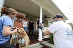 Lisa Fascilla, with children Nina and Alex  receive a beer delivery from Karen and Mark Heuwetter and their two dogs Buddy and Barley on May 03, 2020 in Huntington Village, New York.  Mark and Karen Heuwetter own the Six Harbors Brewery and have trained their two Golden Retrievers Buddy and Barley to help them deliver beer to their customers during the coronavirus COVID-19 pandemic.  The dogs are fitted with a four pack of empty beer cans around their necks and meet customers at their doorstep while Mark and Karen carry the beer to deliver behind them.  It has been comforting for the dogs who are enjoying the exercise and meeting people along the way.  The customers love seeing Buddy and Barley and enjoy petting and greeting them to go with their beer delivery.
