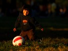 A young child plays a pickup game of soccer as his adult relatives participate in the Fedeiguayas Soccer League on September 2, 2007 at Flushing Meadows Park in Queens, New York.