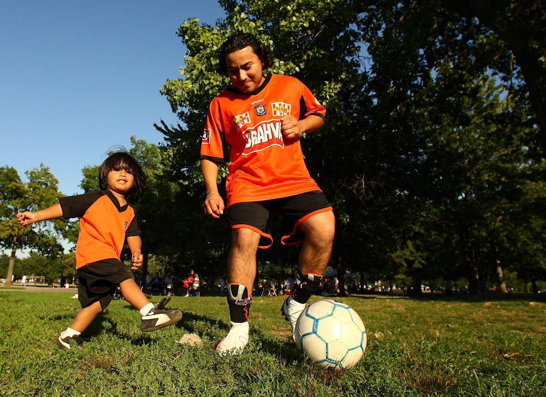 Jose Orellana and his son Jhair of El Salvador now living in Queens play soccer before Jose's Fedeiguayas Soccer League game on September 2, 2007 at Flushing Meadows Park in Queens, New York.