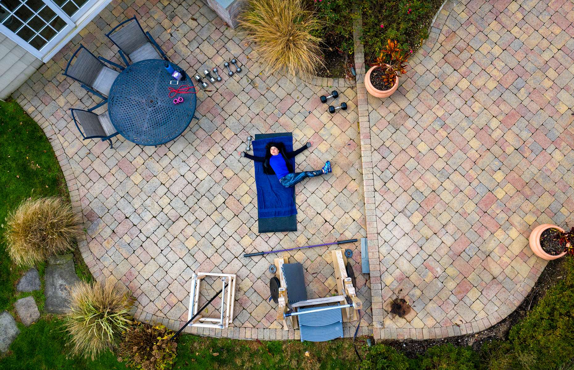 An aerial view of Debbie Krueger exercising in her backyard with her virtual Fitness Trainer Dennis Guerrero on November 17th, 2020 in Hewlett Harbor, New York.  In March of 2014, Dennis Guerrero and his business partner opened a gym on Long Island. The pair shared a passion for fitness, a dream of creating a local community of like-minded people and a willingness to take a risk. Over the next six years, hundreds of members experienced and embraced a unique environment that fostered a palpable energy, helping athletes of all ages and abilities reach their potential.  The gym became a place to share achievements, work through losses and overcome illness. But like so many other businesses, it seemingly had no way of overcoming the financial impact and ongoing uncertainty of a global pandemic. With the arrival of Covid-19, the gym shut its doors back in March, with no idea when it would reopen. The owners, though, were far from done. They lent out every piece of equipment they owned to the gym's members, continued to pay their staff and worked to set up outdoor classes in hopes of keeping their membership active and healthy. As the shutdown stretched on, it became clear that the physical gym was closed for good.  They have since reinvented themselves and are now called Life Outside the Box.  Their business model has changed drastically, and all their workouts have gone virtual.  The workouts are conducted by a small group of fitness trainers led by Guerrero.  The members pay a monthly fee and can take live Zoom fitness classes.  They are coached by the virtual trainers in real time.  More and more people have reconstructed their garages, spare rooms, backyards, and basements into home gyms since the COVID-19 pandemic hit the United States.