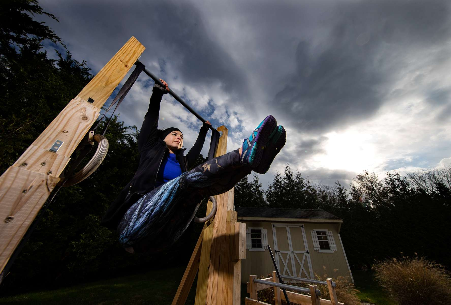 Debbie Krueger exercises in her backyard with her virtual Fitness Trainer Dennis Guerrero on November 17th, 2020 in Hewlett Harbor, New York.  In March of 2014, Dennis Guerrero and his business partner opened a gym on Long Island. The pair shared a passion for fitness, a dream of creating a local community of like-minded people and a willingness to take a risk. Over the next six years, hundreds of members experienced and embraced a unique environment that fostered a palpable energy, helping athletes of all ages and abilities reach their potential.  The gym became a place to share achievements, work through losses and overcome illness. But like so many other businesses, it seemingly had no way of overcoming the financial impact and ongoing uncertainty of a global pandemic. With the arrival of Covid-19, the gym shut its doors back in March, with no idea when it would reopen. The owners, though, were far from done. They lent out every piece of equipment they owned to the gym's members, continued to pay their staff and worked to set up outdoor classes in hopes of keeping their membership active and healthy. As the shutdown stretched on, it became clear that the physical gym was closed for good.  They have since reinvented themselves and are now called Life Outside the Box.  Their business model has changed drastically, and all their workouts have gone virtual.  The workouts are conducted by a small group of fitness trainers led by Guerrero.  The members pay a monthly fee and can take live Zoom fitness classes.  They are coached by the virtual trainers in real time.  More and more people have reconstructed their garages, spare rooms, backyards, and basements into home gyms since the COVID-19 pandemic hit the United States.