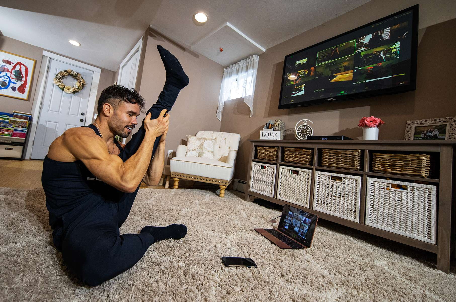 Dennis Guerrero, who is the Co-owner, and Head Trainer of Life Outside the Box fitness leads a virtual exercise class from his living room on November 8th, 2020 in Long Beach, New York. In March of 2014, Dennis Guerrero and his business partner opened a gym on Long Island. The pair shared a passion for fitness, a dream of creating a local community of like-minded people and a willingness to take a risk. Over the next six years, hundreds of members experienced and embraced a unique environment that fostered a palpable energy, helping athletes of all ages and abilities reach their potential.  The gym became a place to share achievements, work through losses and overcome illness. But like so many other businesses, it seemingly had no way of overcoming the financial impact and ongoing uncertainty of a global pandemic. With the arrival of Covid-19, the gym shut its doors back in March, with no idea when it would reopen. The owners, though, were far from done. They lent out every piece of equipment they owned to the gym's members, continued to pay their staff and worked to set up outdoor classes in hopes of keeping their membership active and healthy. As the shutdown stretched on, it became clear that the physical gym was closed for good.  They have since reinvented themselves and are now called Life Outside the Box.  Their business model has changed drastically, and all their workouts have gone virtual.  The workouts are conducted by a small group of fitness trainers led by Guerrero.  The members pay a monthly fee and can take live Zoom fitness classes.  They are coached by the virtual trainers in real time.  More and more people have reconstructed their garages, spare rooms, backyards, and basements into home gyms since the COVID-19 pandemic hit the United States.