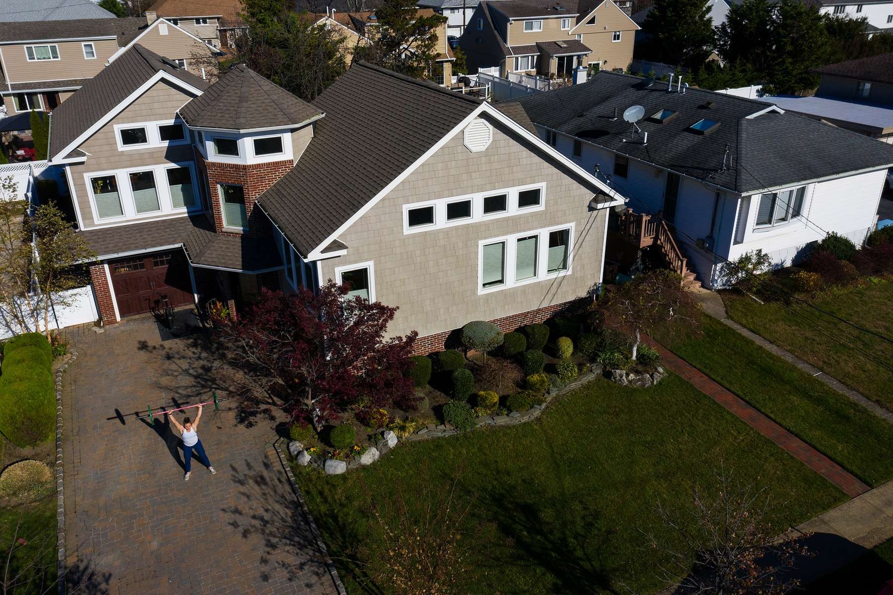 An aerial view of Alexa Hoovis exercising in her driveway after a training session with her virtual Fitness Trainer Dennis Guerrero on November 20th, 2020 in Oceanside, New York.  In March of 2014, Dennis Guerrero and his business partner opened a gym on Long Island. The pair shared a passion for fitness, a dream of creating a local community of like-minded people and a willingness to take a risk. Over the next six years, hundreds of members experienced and embraced a unique environment that fostered a palpable energy, helping athletes of all ages and abilities reach their potential.  The gym became a place to share achievements, work through losses and overcome illness. But like so many other businesses, it seemingly had no way of overcoming the financial impact and ongoing uncertainty of a global pandemic. With the arrival of Covid-19, the gym shut its doors back in March, with no idea when it would reopen. The owners, though, were far from done. They lent out every piece of equipment they owned to the gym's members, continued to pay their staff and worked to set up outdoor classes in hopes of keeping their membership active and healthy. As the shutdown stretched on, it became clear that the physical gym was closed for good.  They have since reinvented themselves and are now called Life Outside the Box.  Their business model has changed drastically, and all their workouts have gone virtual.  The workouts are conducted by a small group of fitness trainers led by Guerrero.  The members pay a monthly fee and can take live Zoom fitness classes.  They are coached by the virtual trainers in real time.  More and more people have reconstructed their garages, spare rooms, backyards, and basements into home gyms since the COVID-19 pandemic hit the United States.