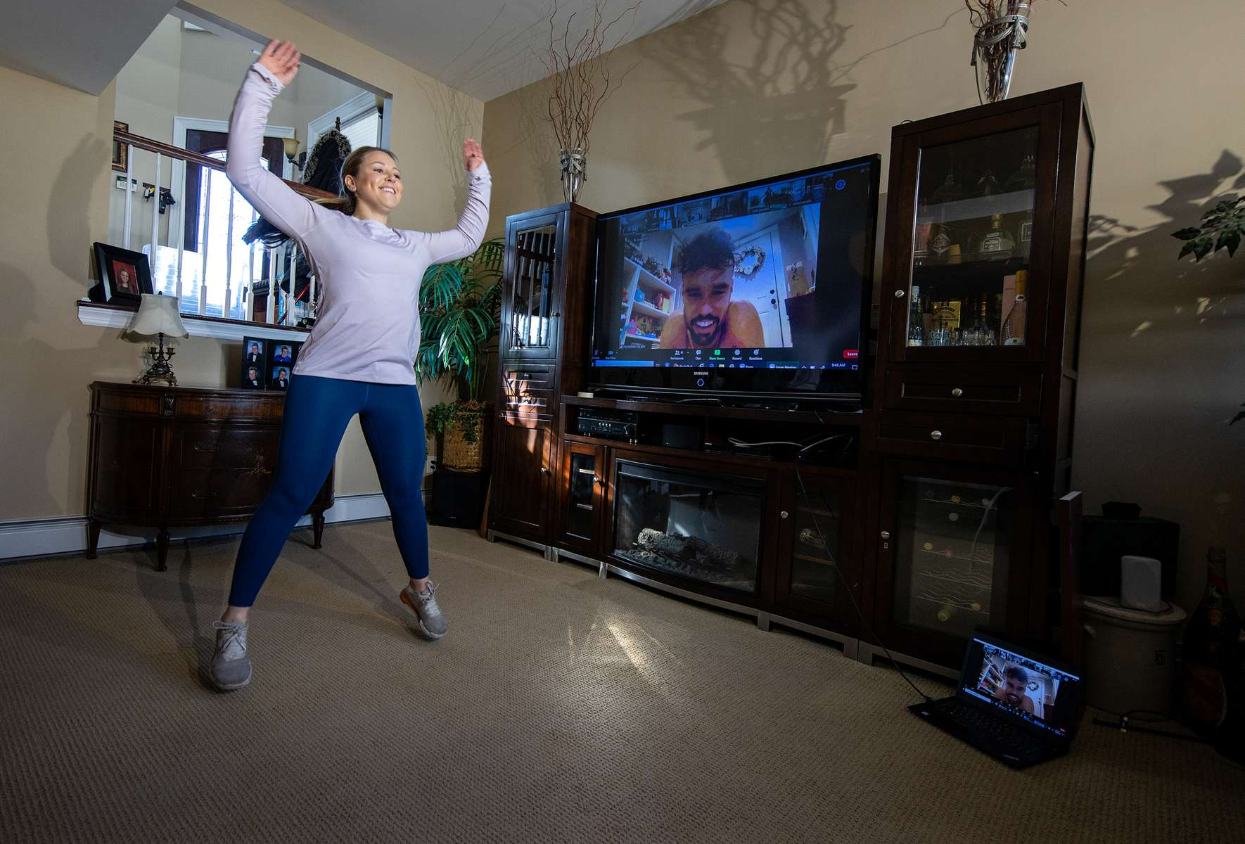 Alexa Hoovis exercises in her home with her virtual Fitness Trainer Dennis Guerrero on November 20th, 2020 in Oceanside, New York.  In March of 2014, Dennis Guerrero and his business partner opened a gym on Long Island. The pair shared a passion for fitness, a dream of creating a local community of like-minded people and a willingness to take a risk. Over the next six years, hundreds of members experienced and embraced a unique environment that fostered a palpable energy, helping athletes of all ages and abilities reach their potential.  The gym became a place to share achievements, work through losses and overcome illness. But like so many other businesses, it seemingly had no way of overcoming the financial impact and ongoing uncertainty of a global pandemic. With the arrival of Covid-19, the gym shut its doors back in March, with no idea when it would reopen. The owners, though, were far from done. They lent out every piece of equipment they owned to the gym's members, continued to pay their staff and worked to set up outdoor classes in hopes of keeping their membership active and healthy. As the shutdown stretched on, it became clear that the physical gym was closed for good.  They have since reinvented themselves and are now called Life Outside the Box.  Their business model has changed drastically, and all their workouts have gone virtual.  The workouts are conducted by a small group of fitness trainers led by Guerrero.  The members pay a monthly fee and can take live Zoom fitness classes.  They are coached by the virtual trainers in real time.  More and more people have reconstructed their garages, spare rooms, backyards, and basements into home gyms since the COVID-19 pandemic hit the United States.