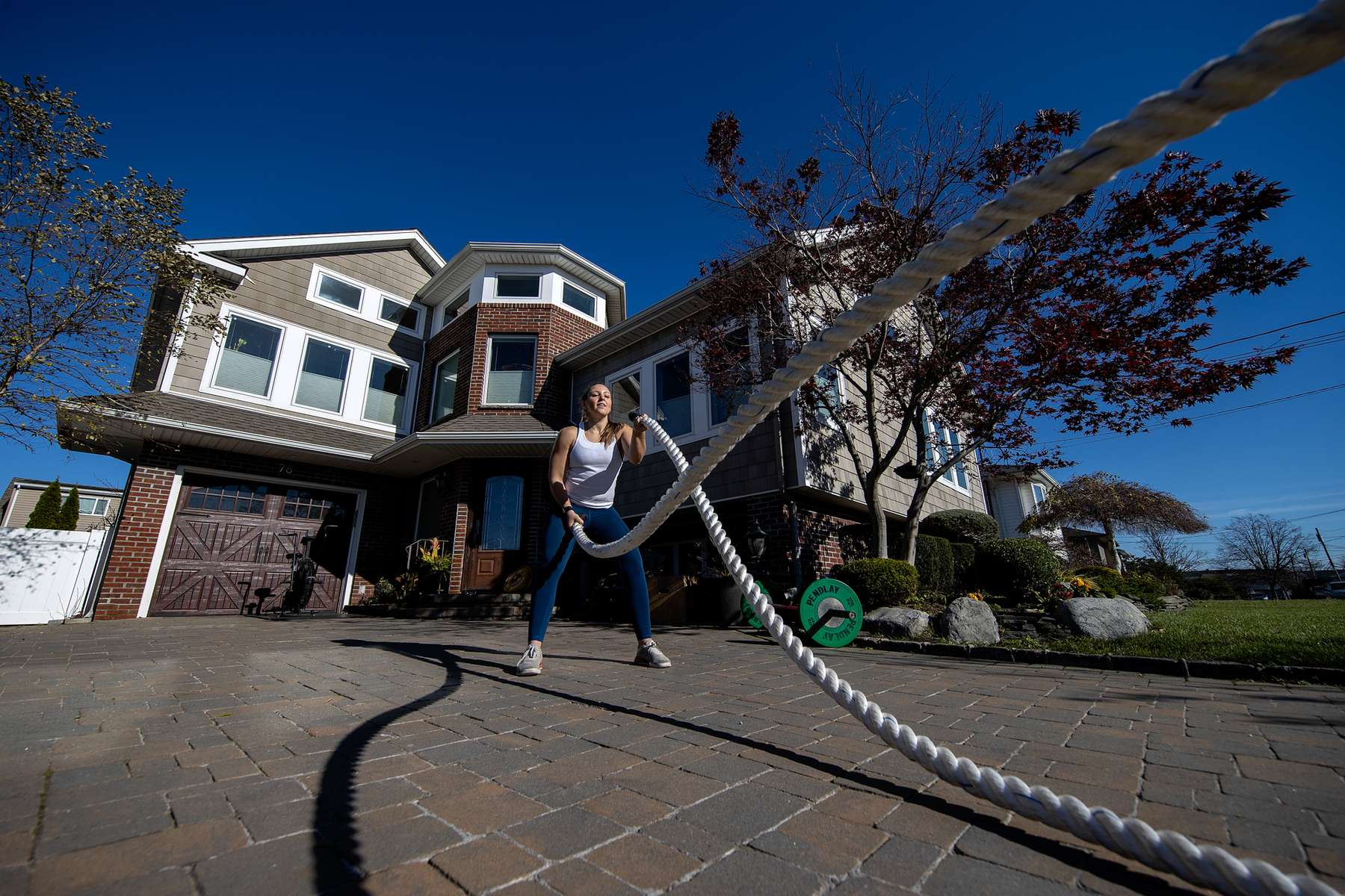 Alexa Hoovis exercises in her driveway with her virtual Fitness Trainer Dennis Guerrero on November 20th, 2020 in Oceanside, New York.  In March of 2014, Dennis Guerrero and his business partner opened a gym on Long Island. The pair shared a passion for fitness, a dream of creating a local community of like-minded people and a willingness to take a risk. Over the next six years, hundreds of members experienced and embraced a unique environment that fostered a palpable energy, helping athletes of all ages and abilities reach their potential.  The gym became a place to share achievements, work through losses and overcome illness. But like so many other businesses, it seemingly had no way of overcoming the financial impact and ongoing uncertainty of a global pandemic. With the arrival of Covid-19, the gym shut its doors back in March, with no idea when it would reopen. The owners, though, were far from done. They lent out every piece of equipment they owned to the gym's members, continued to pay their staff and worked to set up outdoor classes in hopes of keeping their membership active and healthy. As the shutdown stretched on, it became clear that the physical gym was closed for good.  They have since reinvented themselves and are now called Life Outside the Box.  Their business model has changed drastically, and all their workouts have gone virtual.  The workouts are conducted by a small group of fitness trainers led by Guerrero.  The members pay a monthly fee and can take live Zoom fitness classes.  They are coached by the virtual trainers in real time.  More and more people have reconstructed their garages, spare rooms, backyards, and basements into home gyms since the COVID-19 pandemic hit the United States.
