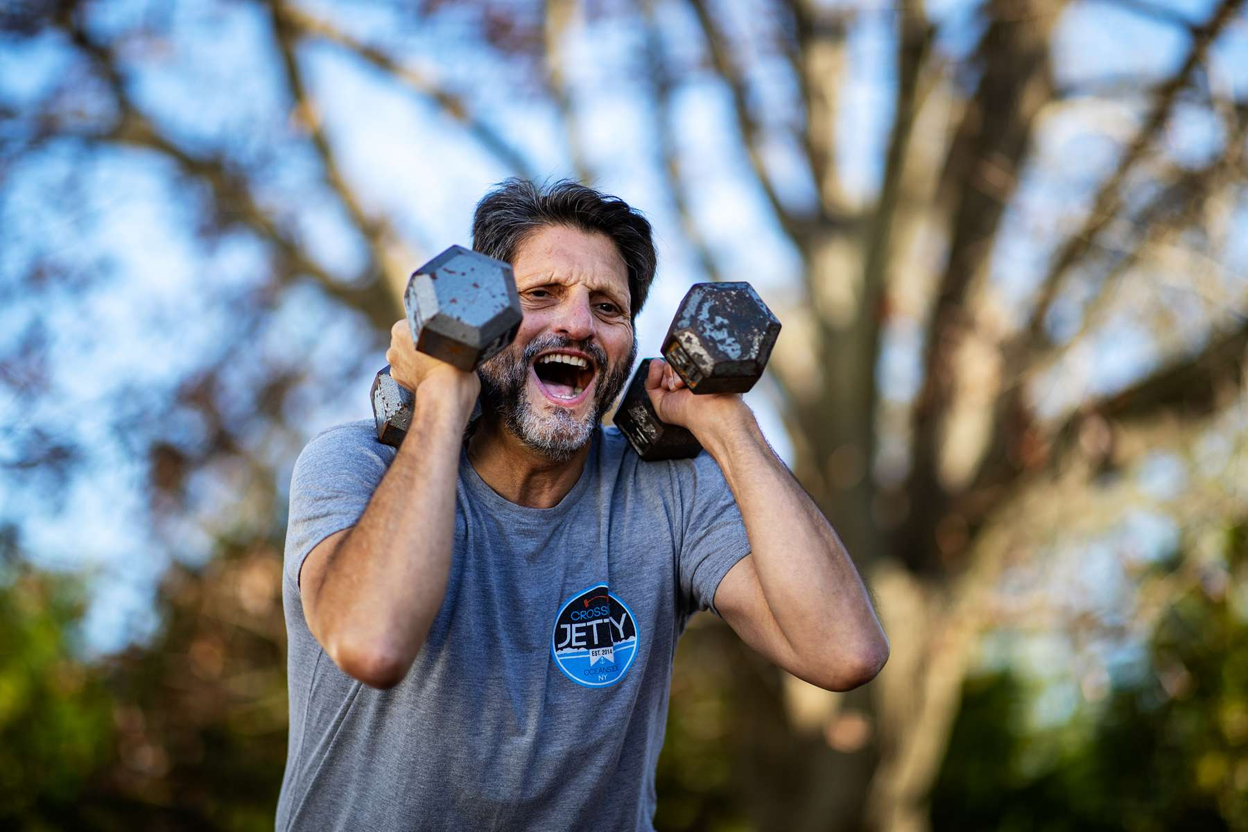 Jeff Levine exercises in his backyard with his virtual Fitness Trainer Dennis Guerrero on November 10th, 2020 in Oceanside, New York. In March of 2014, Dennis Guerrero and his business partner opened a gym on Long Island. The pair shared a passion for fitness, a dream of creating a local community of like-minded people and a willingness to take a risk. Over the next six years, hundreds of members experienced and embraced a unique environment that fostered a palpable energy, helping athletes of all ages and abilities reach their potential.  The gym became a place to share achievements, work through losses and overcome illness. But like so many other businesses, it seemingly had no way of overcoming the financial impact and ongoing uncertainty of a global pandemic. With the arrival of Covid-19, the gym shut its doors back in March, with no idea when it would reopen. The owners, though, were far from done. They lent out every piece of equipment they owned to the gym's members, continued to pay their staff and worked to set up outdoor classes in hopes of keeping their membership active and healthy. As the shutdown stretched on, it became clear that the physical gym was closed for good.  They have since reinvented themselves and are now called Life Outside the Box.  Their business model has changed drastically, and all their workouts have gone virtual.  The workouts are conducted by a small group of fitness trainers led by Guerrero.  The members pay a monthly fee and can take live Zoom fitness classes.  They are coached by the virtual trainers in real time.  More and more people have reconstructed their garages, spare rooms, backyards, and basements into home gyms since the COVID-19 pandemic hit the United States.