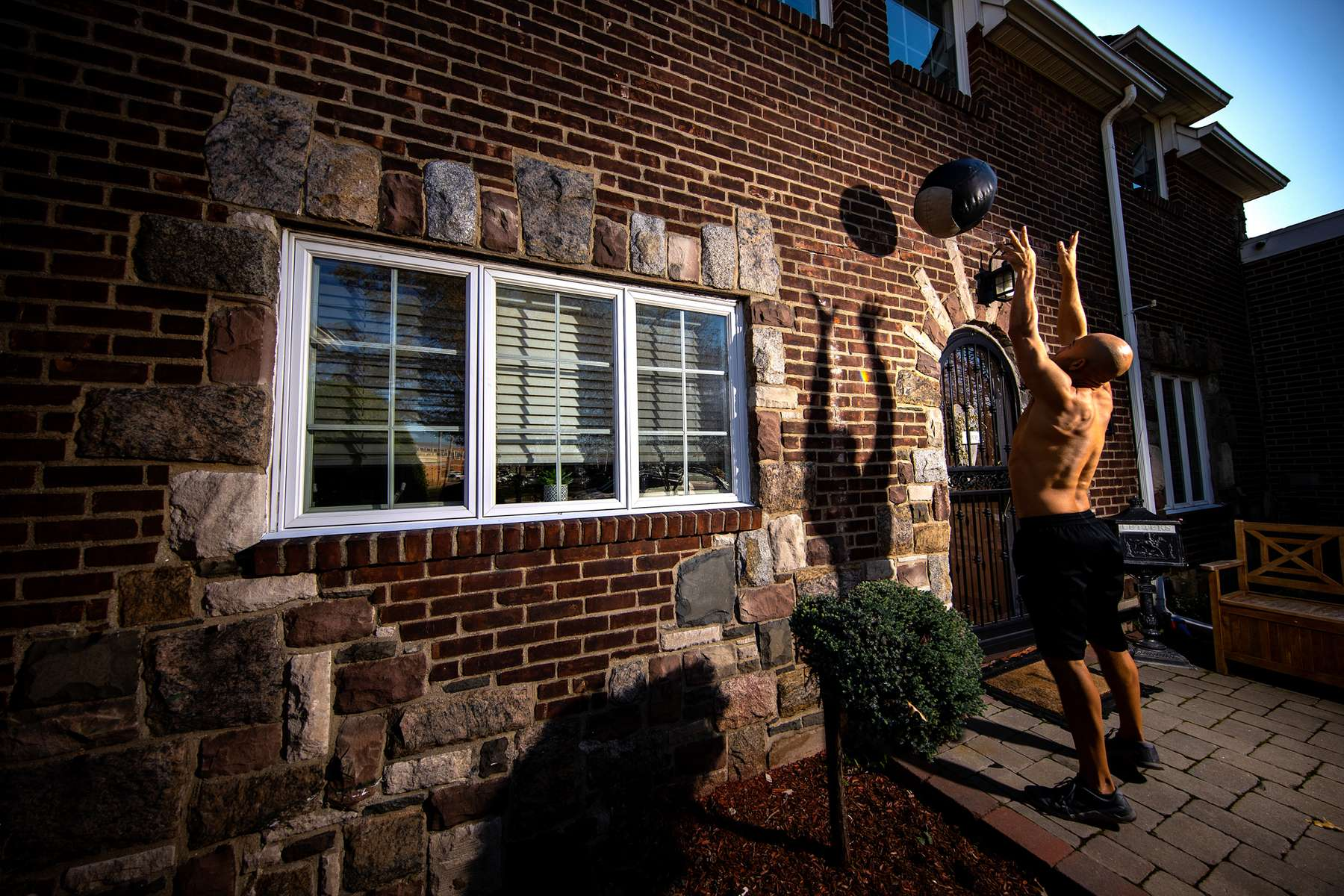 Loneil Jenkins exercises in front of his home with his virtual Fitness Trainer Dennis Guerrero on November 9th, 2020 in Oceanside, New York.  In March of 2014, Dennis Guerrero and his business partner opened a gym on Long Island. The pair shared a passion for fitness, a dream of creating a local community of like-minded people and a willingness to take a risk. Over the next six years, hundreds of members experienced and embraced a unique environment that fostered a palpable energy, helping athletes of all ages and abilities reach their potential.  The gym became a place to share achievements, work through losses and overcome illness. But like so many other businesses, it seemingly had no way of overcoming the financial impact and ongoing uncertainty of a global pandemic. With the arrival of Covid-19, the gym shut its doors back in March, with no idea when it would reopen. The owners, though, were far from done. They lent out every piece of equipment they owned to the gym's members, continued to pay their staff and worked to set up outdoor classes in hopes of keeping their membership active and healthy. As the shutdown stretched on, it became clear that the physical gym was closed for good.  They have since reinvented themselves and are now called Life Outside the Box.  Their business model has changed drastically, and all their workouts have gone virtual.  The workouts are conducted by a small group of fitness trainers led by Guerrero.  The members pay a monthly fee and can take live Zoom fitness classes.  They are coached by the virtual trainers in real time.  More and more people have reconstructed their garages, spare rooms, backyards, and basements into home gyms since the COVID-19 pandemic hit the United States.