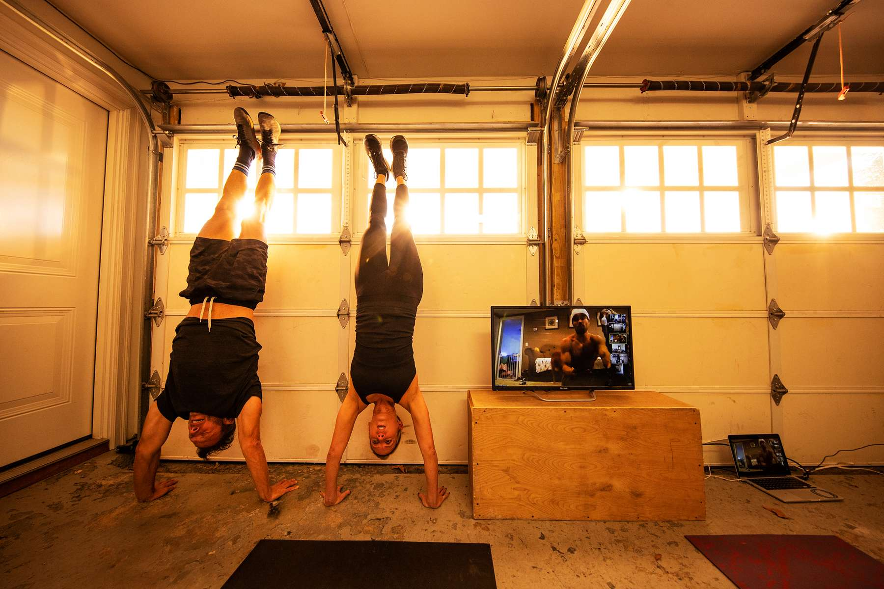 Jamie and Chris Morgan exercise with their virtual Fitness Trainer Dennis Guerrero in their garage on November 3rd, 2020 in Oceanside, New York.  In March of 2014, Dennis Guerrero and his business partner opened a gym on Long Island. The pair shared a passion for fitness, a dream of creating a local community of like-minded people and a willingness to take a risk. Over the next six years, hundreds of members experienced and embraced a unique environment that fostered a palpable energy, helping athletes of all ages and abilities reach their potential.  The gym became a place to share achievements, work through losses and overcome illness. But like so many other businesses, it seemingly had no way of overcoming the financial impact and ongoing uncertainty of a global pandemic. With the arrival of Covid-19, the gym shut its doors back in March, with no idea when it would reopen. The owners, though, were far from done. They lent out every piece of equipment they owned to the gym's members, continued to pay their staff and worked to set up outdoor classes in hopes of keeping their membership active and healthy. As the shutdown stretched on, it became clear that the physical gym was closed for good.  They have since reinvented themselves and are now called Life Outside the Box.  Their business model has changed drastically, and all their workouts have gone virtual.  The workouts are conducted by a small group of fitness trainers led by Guerrero.  The members pay a monthly fee and can take live Zoom fitness classes.  They are coached by the virtual trainers in real time.  More and more people have reconstructed their garages, spare rooms, backyards, and basements into home gyms since the COVID-19 pandemic hit the United States.