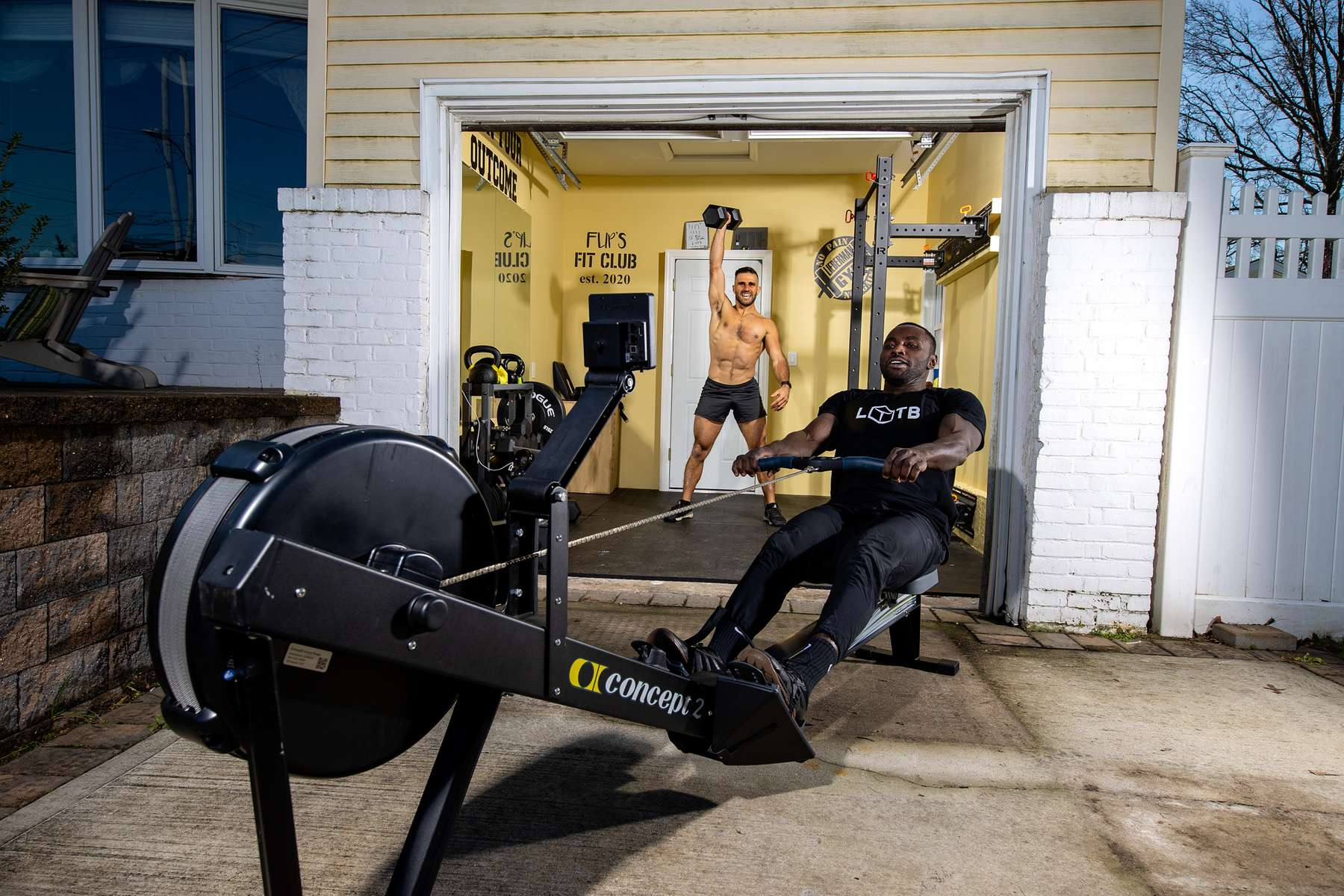 John Puccio and Raheem Yusuff exercise in a friend's garage with their virtual Fitness Trainer Dennis Guerrero on November 14th, 2020 in Oceanside, New York.  In March of 2014, Dennis Guerrero and his business partner opened a gym on Long Island. The pair shared a passion for fitness, a dream of creating a local community of like-minded people and a willingness to take a risk. Over the next six years, hundreds of members experienced and embraced a unique environment that fostered a palpable energy, helping athletes of all ages and abilities reach their potential.  The gym became a place to share achievements, work through losses and overcome illness. But like so many other businesses, it seemingly had no way of overcoming the financial impact and ongoing uncertainty of a global pandemic. With the arrival of Covid-19, the gym shut its doors back in March, with no idea when it would reopen. The owners, though, were far from done. They lent out every piece of equipment they owned to the gym's members, continued to pay their staff and worked to set up outdoor classes in hopes of keeping their membership active and healthy. As the shutdown stretched on, it became clear that the physical gym was closed for good.  They have since reinvented themselves and are now called Life Outside the Box.  Their business model has changed drastically, and all their workouts have gone virtual.  The workouts are conducted by a small group of fitness trainers led by Guerrero.  The members pay a monthly fee and can take live Zoom fitness classes.  They are coached by the virtual trainers in real time.  More and more people have reconstructed their garages, spare rooms, backyards, and basements into home gyms since the COVID-19 pandemic hit the United States.