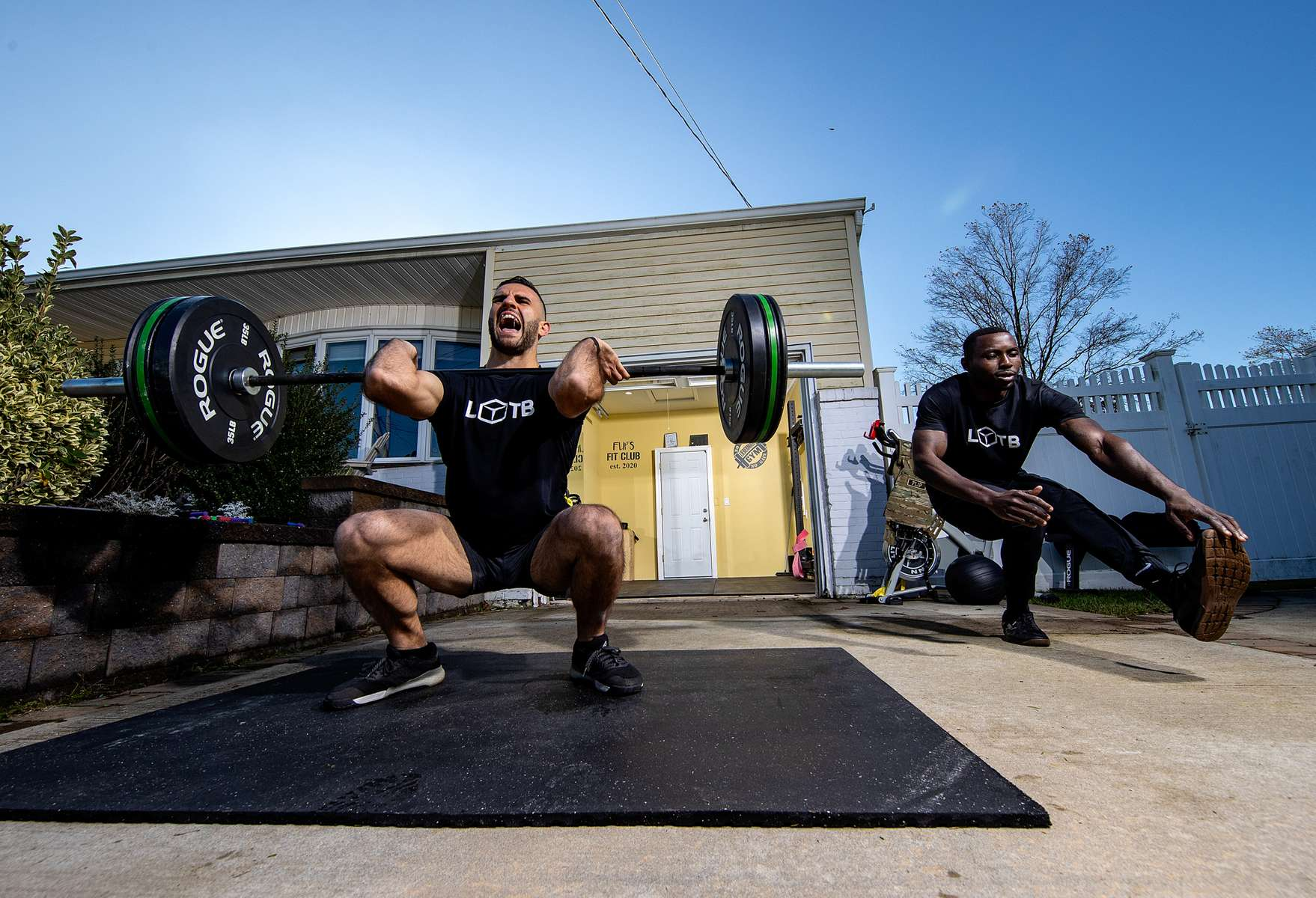 John Puccio and Raheem Yusuff exercise outside a friend's garage with their virtual Fitness Trainer Dennis Guerrero on November 14th, 2020 in Oceanside, New York.  In March of 2014, Dennis Guerrero and his business partner opened a gym on Long Island. The pair shared a passion for fitness, a dream of creating a local community of like-minded people and a willingness to take a risk. Over the next six years, hundreds of members experienced and embraced a unique environment that fostered a palpable energy, helping athletes of all ages and abilities reach their potential.  The gym became a place to share achievements, work through losses and overcome illness. But like so many other businesses, it seemingly had no way of overcoming the financial impact and ongoing uncertainty of a global pandemic. With the arrival of Covid-19, the gym shut its doors back in March, with no idea when it would reopen. The owners, though, were far from done. They lent out every piece of equipment they owned to the gym's members, continued to pay their staff and worked to set up outdoor classes in hopes of keeping their membership active and healthy. As the shutdown stretched on, it became clear that the physical gym was closed for good.  They have since reinvented themselves and are now called Life Outside the Box.  Their business model has changed drastically, and all their workouts have gone virtual.  The workouts are conducted by a small group of fitness trainers led by Guerrero.  The members pay a monthly fee and can take live Zoom fitness classes.  They are coached by the virtual trainers in real time.  More and more people have reconstructed their garages, spare rooms, backyards, and basements into home gyms since the COVID-19 pandemic hit the United States.