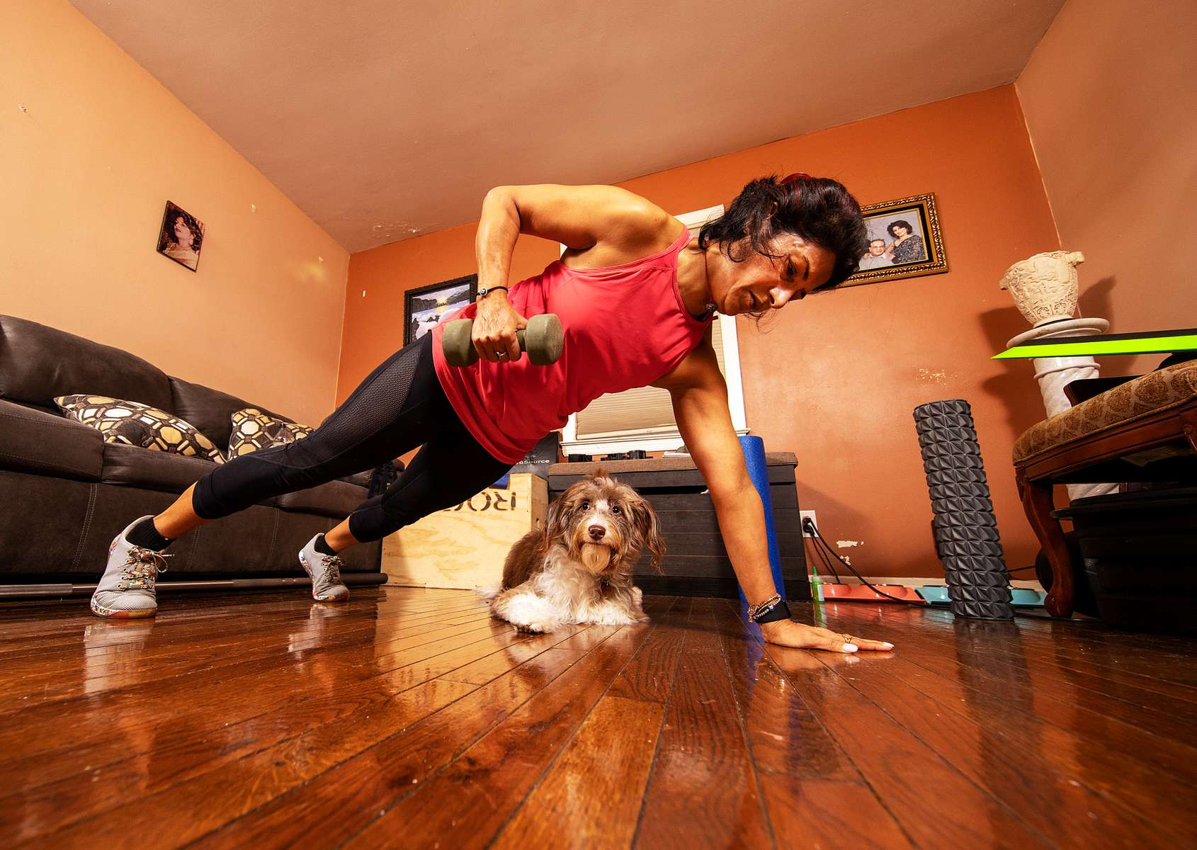 Anu Mago exercises with her virtual Fitness Trainer Dennis Guerrero as her dog Luna watches on October 30, 2020 in Baldwin, New York.  In March of 2014, Dennis Guerrero and his business partner opened a gym on Long Island. The pair shared a passion for fitness, a dream of creating a local community of like-minded people and a willingness to take a risk. Over the next six years, hundreds of members experienced and embraced a unique environment that fostered a palpable energy, helping athletes of all ages and abilities reach their potential.  The gym became a place to share achievements, work through losses and overcome illness. But like so many other businesses, it seemingly had no way of overcoming the financial impact and ongoing uncertainty of a global pandemic. With the arrival of Covid-19, the gym shut its doors back in March, with no idea when it would reopen. The owners, though, were far from done. They lent out every piece of equipment they owned to the gym's members, continued to pay their staff and worked to set up outdoor classes in hopes of keeping their membership active and healthy. As the shutdown stretched on, it became clear that the physical gym was closed for good.  They have since reinvented themselves and are now called Life Outside the Box.  Their business model has changed drastically, and all their workouts have gone virtual.  The workouts are conducted by a small group of fitness trainers led by Guerrero.  The members pay a monthly fee and can take live Zoom fitness classes.  They are coached by the virtual trainers in real time.  More and more people have reconstructed their garages, spare rooms, backyards, and basements into home gyms since the COVID-19 pandemic hit the United States.