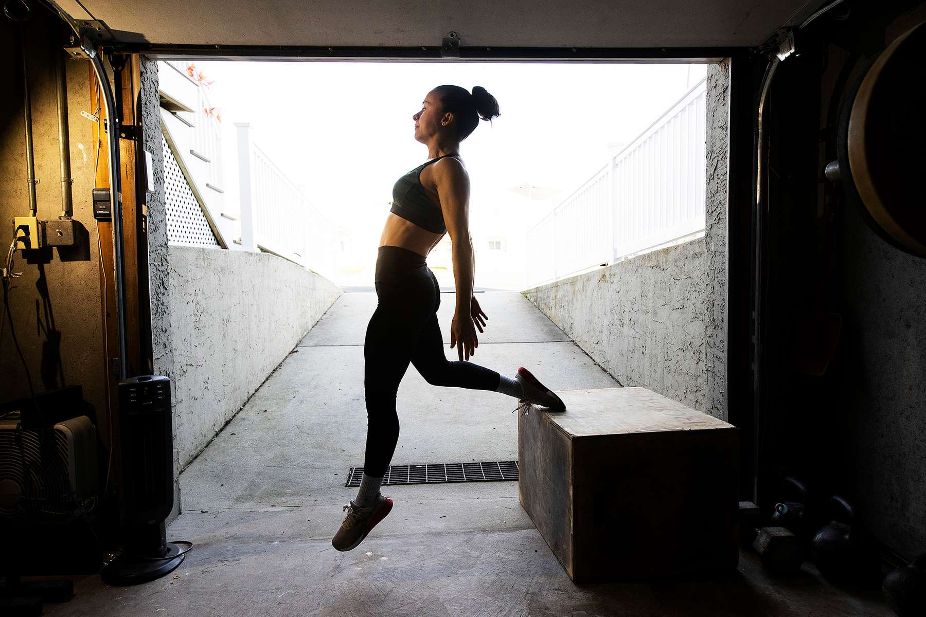 LONG BEACH, NEW YORK - NOVEMBER 21:  Nicole Guerrero exercises in her garage with her virtual Fitness Trainer and Husband Dennis Guerrero on November 21st, 2020 in Long Beach, New York. In March of 2014, Dennis Guerrero and his business partner opened a gym on Long Island. The pair shared a passion for fitness, a dream of creating a local community of like-minded people and a willingness to take a risk. Over the next six years, hundreds of members experienced and embraced a unique environment that fostered a palpable energy, helping athletes of all ages and abilities reach their potential.  The gym became a place to share achievements, work through losses and overcome illness. But like so many other businesses, it seemingly had no way of overcoming the financial impact and ongoing uncertainty of a global pandemic. With the arrival of Covid-19, the gym shut its doors back in March, with no idea when it would reopen. The owners, though, were far from done. They lent out every piece of equipment they owned to the gym's members, continued to pay their staff and worked to set up outdoor classes in hopes of keeping their membership active and healthy. As the shutdown stretched on, it became clear that the physical gym was closed for good.  They have since reinvented themselves and are now called Life Outside the Box.  Their business model has changed drastically, and all their workouts have gone virtual.  The workouts are conducted by a small group of fitness trainers led by Guerrero.  The members pay a monthly fee and can take live Zoom fitness classes.  They are coached by the virtual trainers in real time.  More and more people have reconstructed their garages, spare rooms, backyards, and basements into home gyms since the COVID-19 pandemic hit the United States.  (Photo by Al Bello/Getty Images)