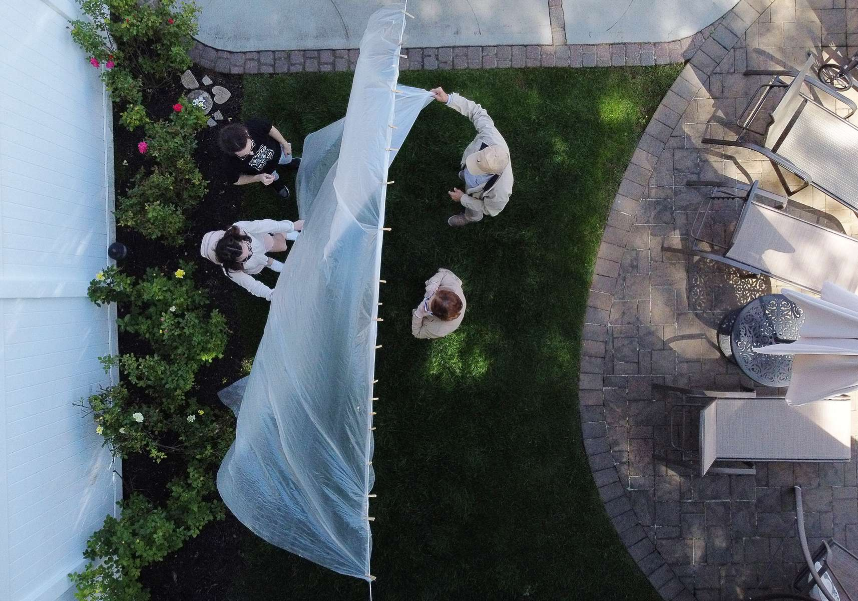 An aerial view of Olivia and James Grant hug their Grandparents Mary Grace and Domenik Sileo through a plastic drop cloth hung up on a homemade clothes line during Memorial Day Weekend on May 24, 2020 in Wantagh, New York.  It is the first time they have had physical contact of any kind since the coronavirus COVID-19 pandemic lockdown started in late February.