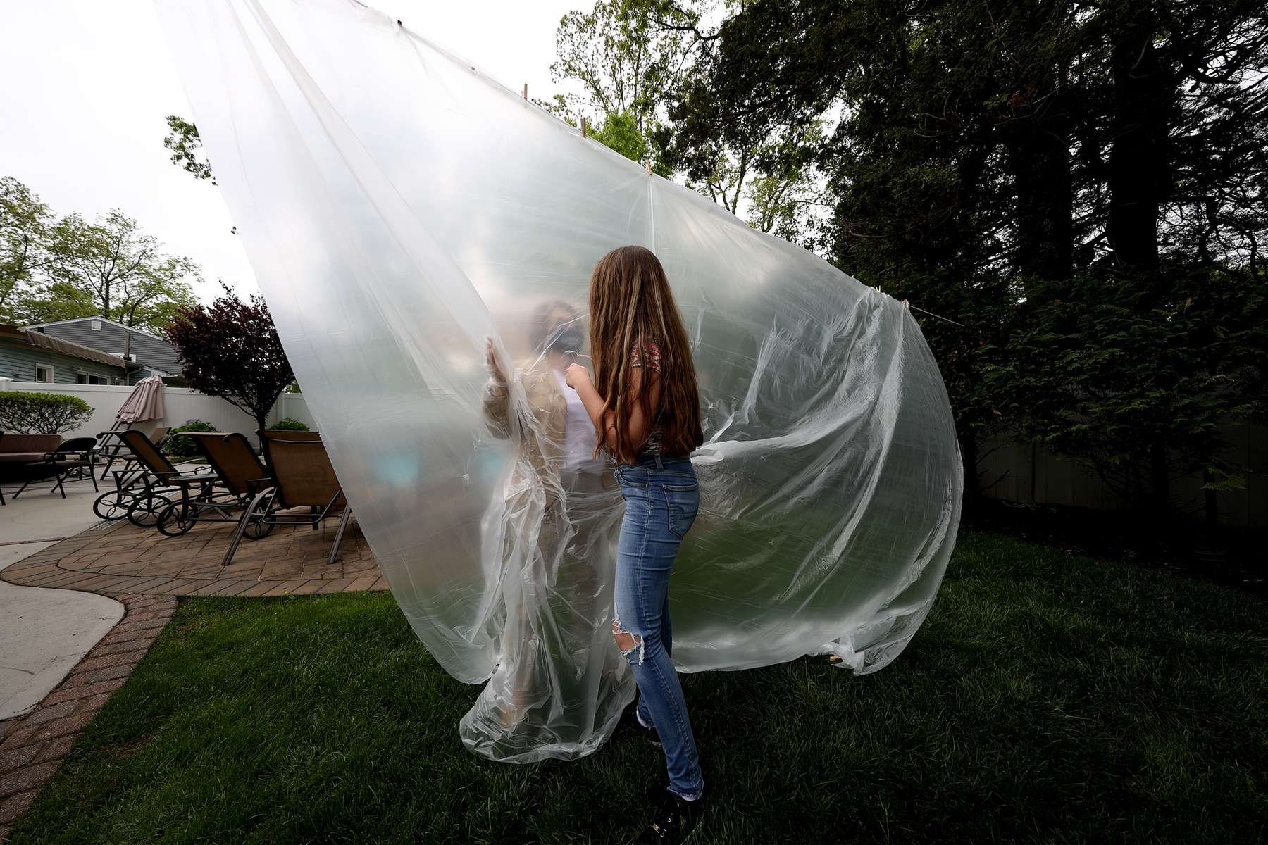 Julia Sileo hugs her Grandmother Mary Grace Sileo through a plastic drop cloth hung up on a homemade clothes line during Memorial Day Weekend on May 24, 2020 in Wantagh, New York.  It is the first time they have had physical contact of any kind since the coronavirus COVID-19 pandemic lockdown started in late February.