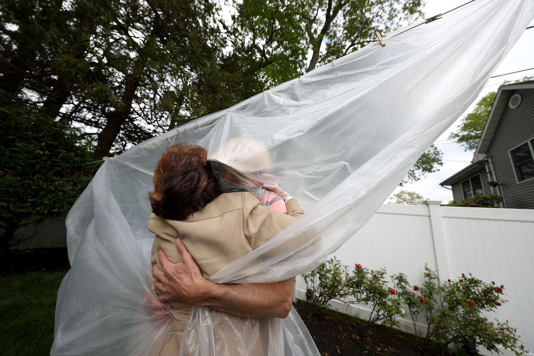 rank Sileo hugs his Mother Mary Grace Sileo through a plastic drop cloth hung up on a homemade clothes line during Memorial Day Weekend on May 24, 2020 in Wantagh, New York.  It is the first time they have had physical contact of any kind since the coronavirus COVID-19 pandemic lockdown started in late February.