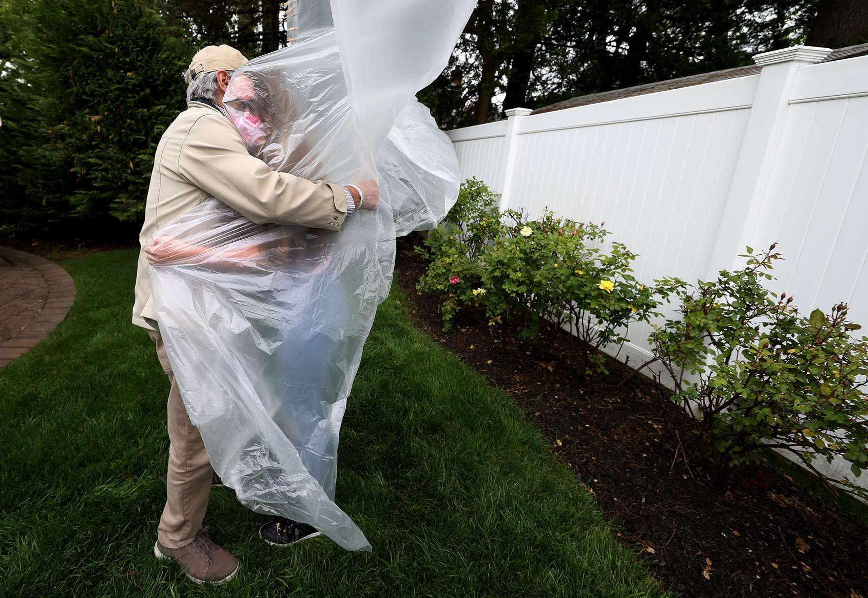 Julia Sileo hugs her Grandfather Domenik Sileo through a plastic drop cloth hung up on a homemade clothes line during Memorial Day Weekend on May 24, 2020 in Wantagh, New York.  It is the first time they have had physical contact of any kind since the coronavirus COVID-19 pandemic lockdown started in late February.