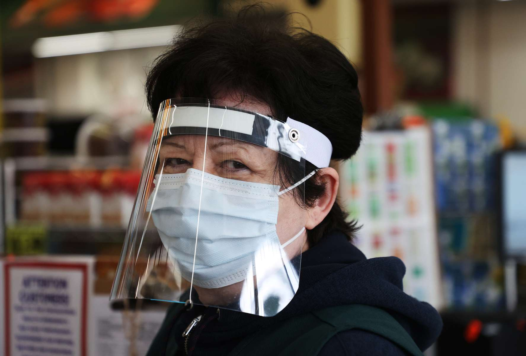 A Pat's Farms grocery store cashier looks on wearing a mask, and plastic visor on March 31, 2020 in Merrick, New York.   The World Health Organization declared coronavirus (COVID-19) a global pandemic on March 11th.