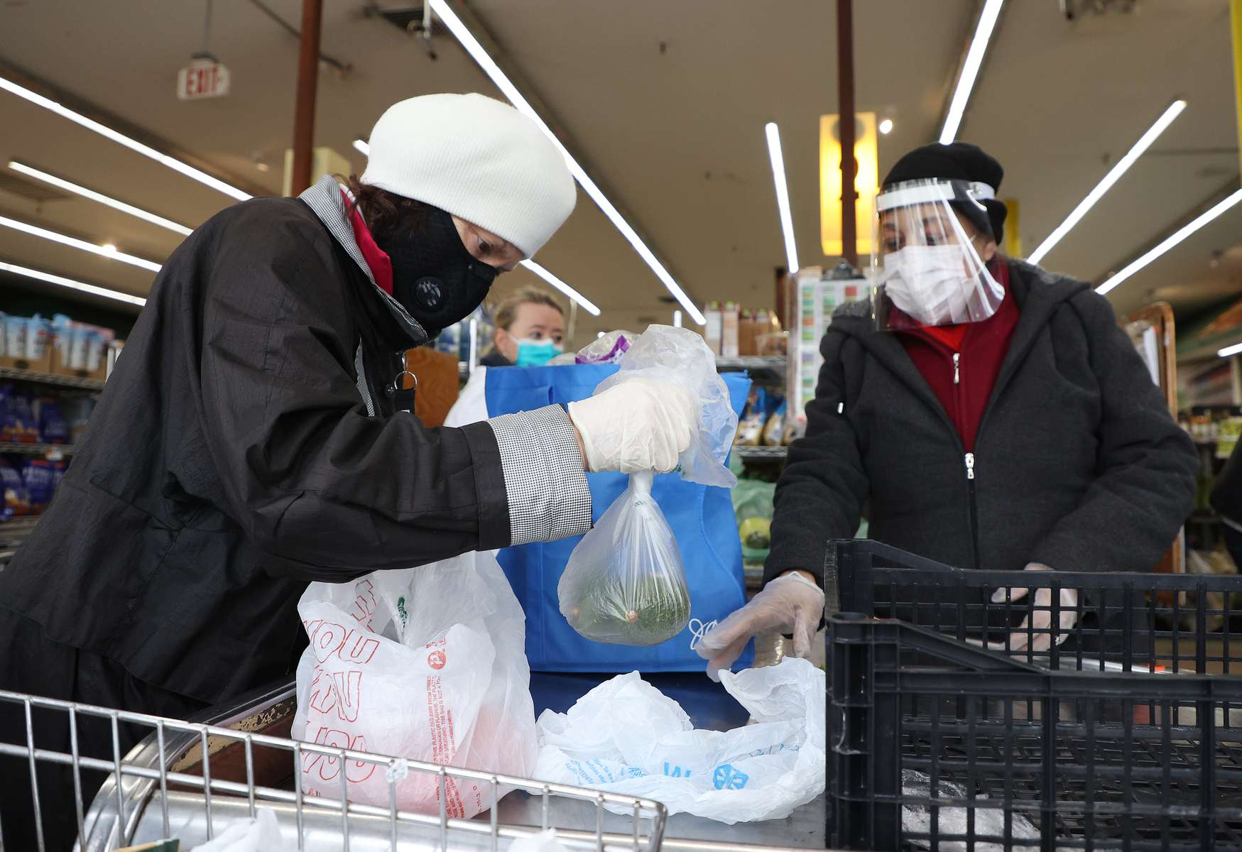 A shopper and cashier both wear masks, gloves and the cashier also has on a plastic visor at the checkout station Pat's Farms grocery store on March 31, 2020 in Merrick, New York.   The World Health Organization declared coronavirus (COVID-19) a global pandemic on March 11th.