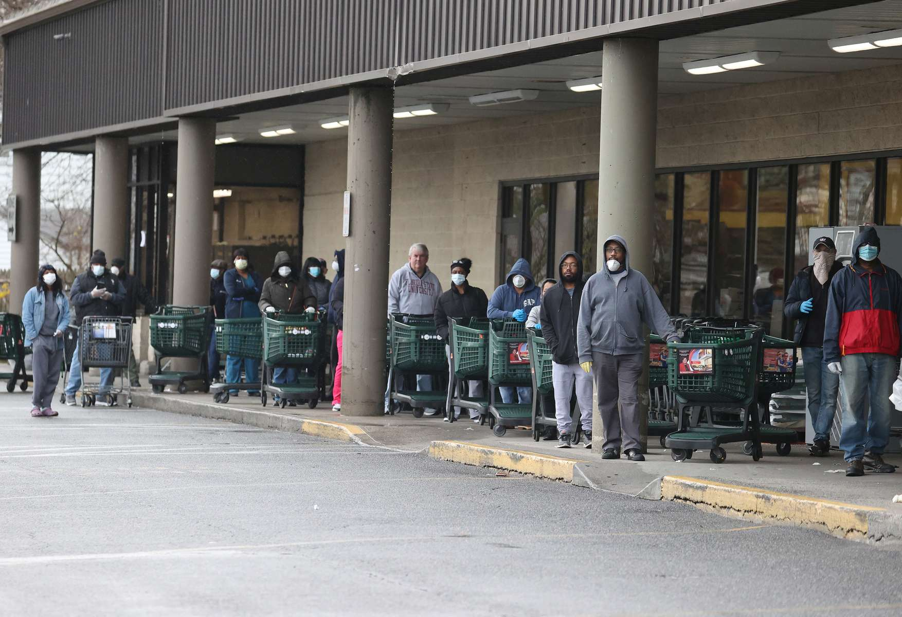 People wearing masks wait to enter Shop Rite on April 03, 2020 in Uniondale, New York.  Due to the coronavirus (COVID-19) pandemic the supermarket has  implemented social distancing while shopping in the store by letting only a certain number of people enter at a time.  The World Health Organization declared coronavirus (COVID-19) a global pandemic on March 11th.