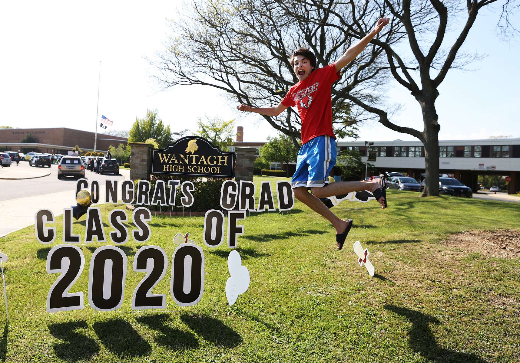 WANTAGH, NEW YORK - MAY 15:  John Sileo, Wantagh High School Co-President class of 2020 poses in front of a sign on the grass as graduating Seniors from Wantagh High School drive by the front of the school and their teachers cheer for them on May 15, 2020 in Wantagh, New York.  The school semester  has been cancelled and students had to finish their year with online video classes due to the coronavirus COVID-19 pandemic.  (Photo by Al Bello/Getty Images)