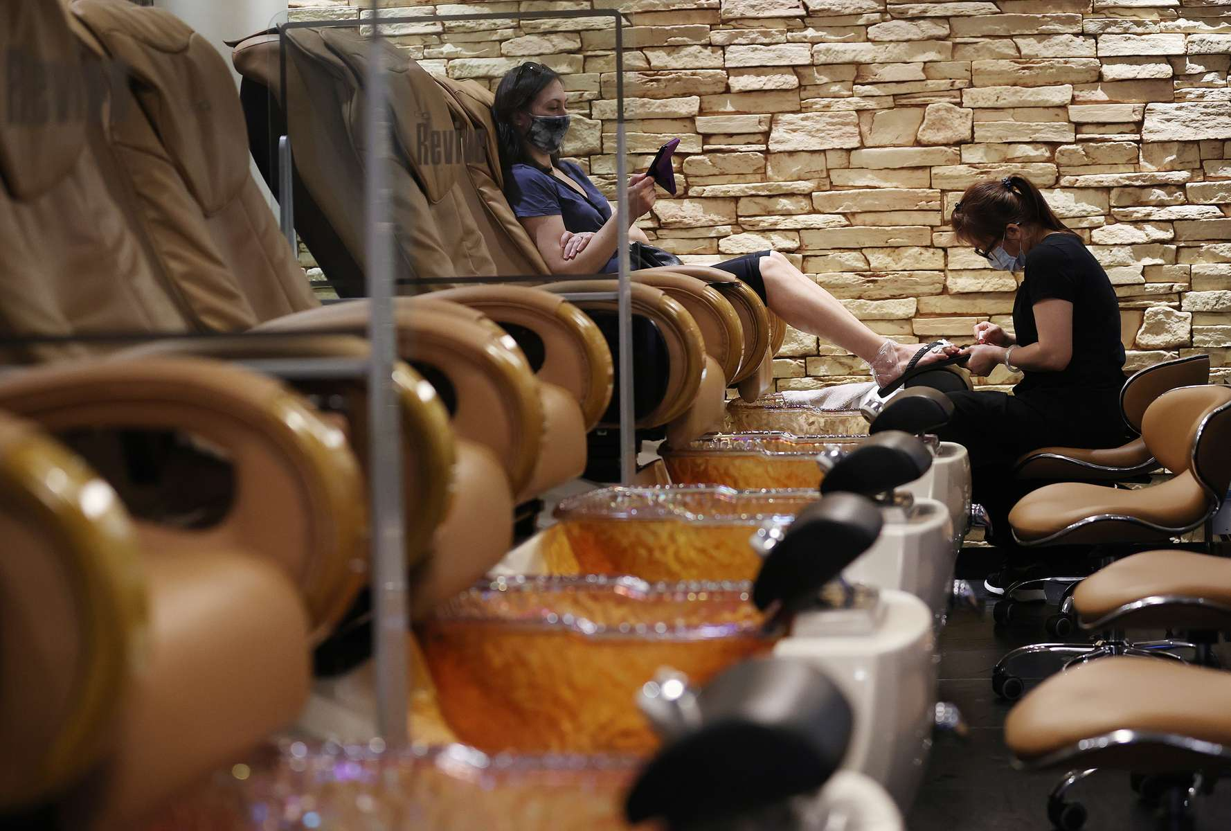 Cynthia Lee does a pedicure for a customer at Revive Nails and Spa as Long Island begins Phase 3 of reopening, allowing restaurants To Seat Inside At 50 Percent Capacity and nail salons to open by appointment only on June 24, 2020 in Huntington, New York.