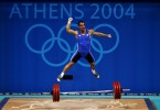 Pyrros Dimas of Greece jumps in the air as he celebrates a successful lift in  the men's 85 kg category weightlifting competition on August 21, 2004 during the Athens 2004 Summer Olympic Games at Nikaia Olympic Weightlifting Hall in Athens, Greece.