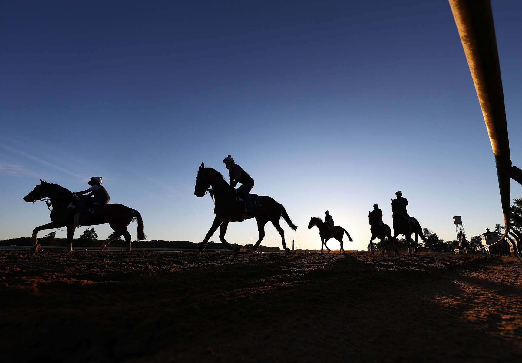Exercise riders and Racehorses enter the main track during morning training prior to the 152nd running of the Belmont Stakes at Belmont Park on June 17, 2020 in Elmont, New York.