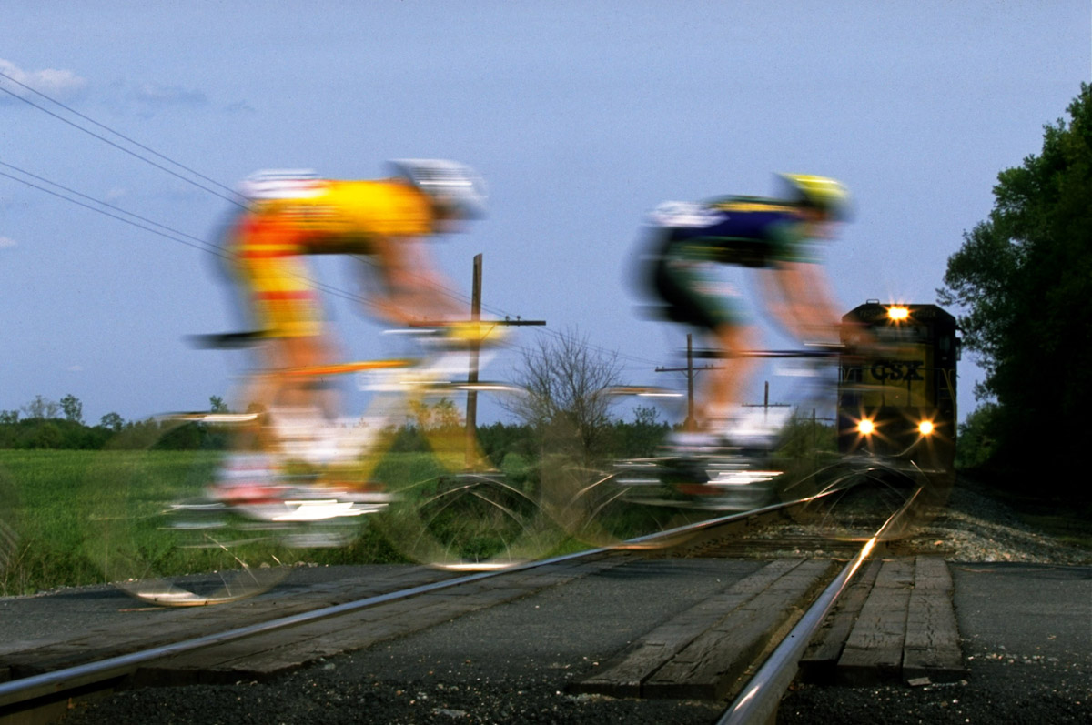 Cyclists race across a railroad crossing on to the path of an oncoming train during Stage 2 of the Tour DuPont between Fredricksburg in Maryland to Richmond on May 6, 1996 in Virginia, USA.