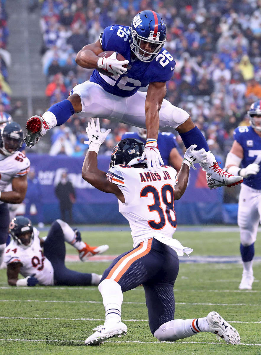 Saquon Barkley #26 of the New York Giants leaps over Adrian Amos #38 of the Chicago Bears for extra yardage during the third quarter at MetLife Stadium on December 02, 2018 in East Rutherford, New Jersey.
