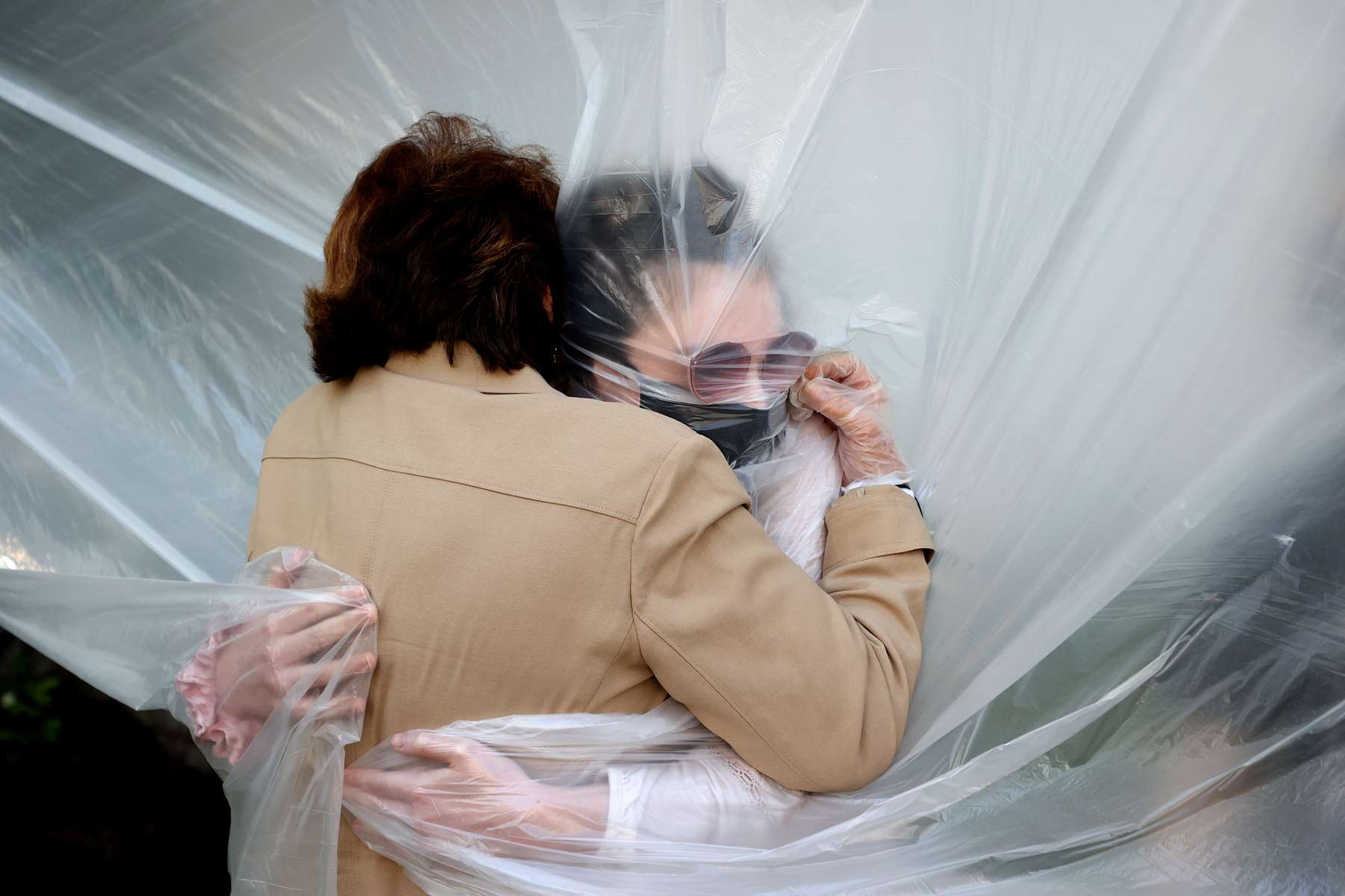 Olivia Grant hugs her Grandmother Mary Grace Sileo through a plastic drop cloth hung up on a homemade clothes line during Memorial Day Weekend on May 24, 2020 in Wantagh, New York.  It is the first time they have had contact of any kind since the coronavirus COVID-19 pandemic lockdown started in late February.