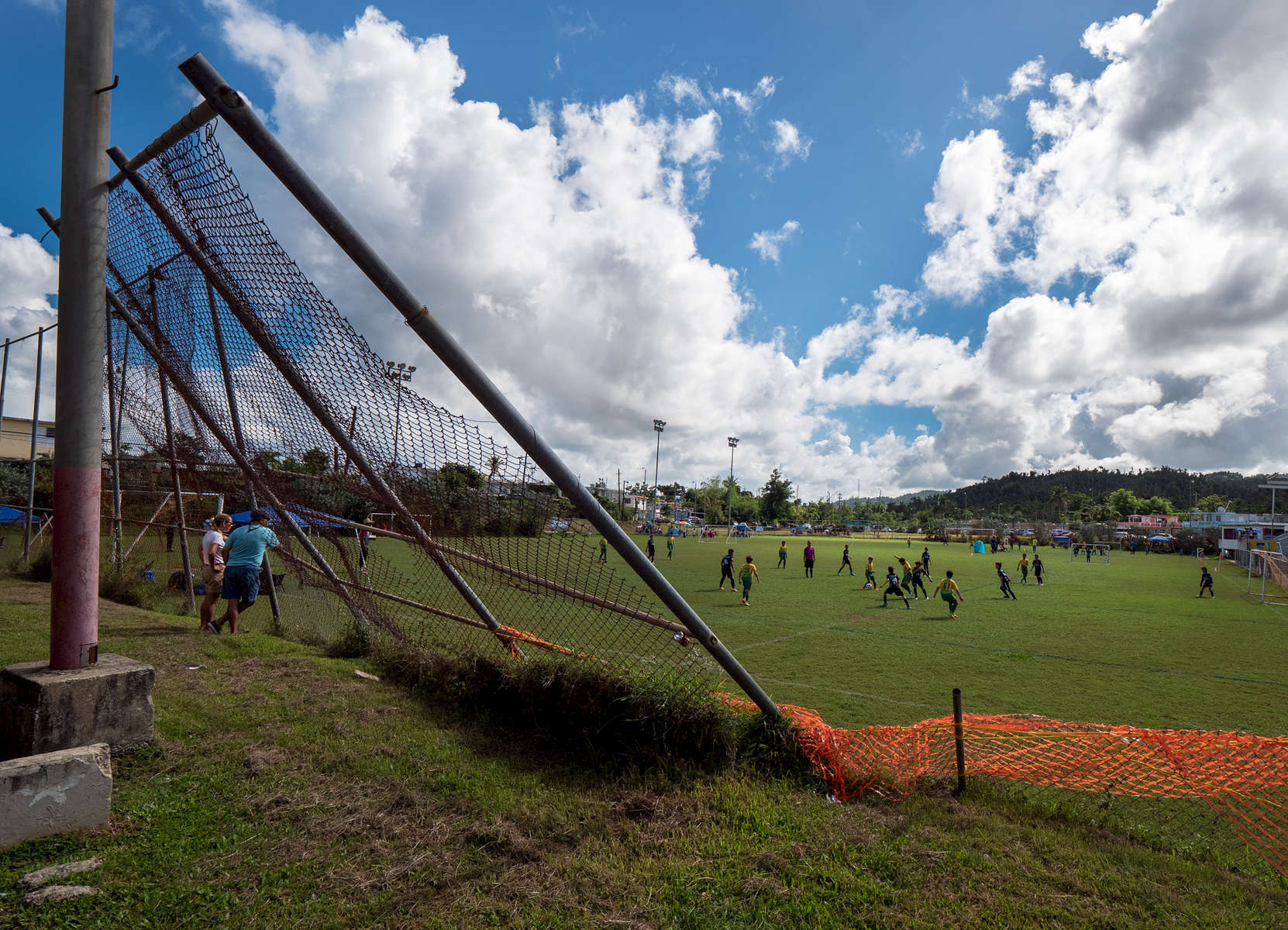 CAGUAS, PUERTO RICO - NOVEMBER 10: Little League Soccer players compete by a fallen fence caused by Hurricane Maria on November 10, 2018 in Caguas, Puerto Rico. The effort continues in Puerto Rico to remain and rebuild more than one year after the Hurricane Maria hit and devastated the island on September 20, 2017. The official number of deaths from the disaster is 2,975.