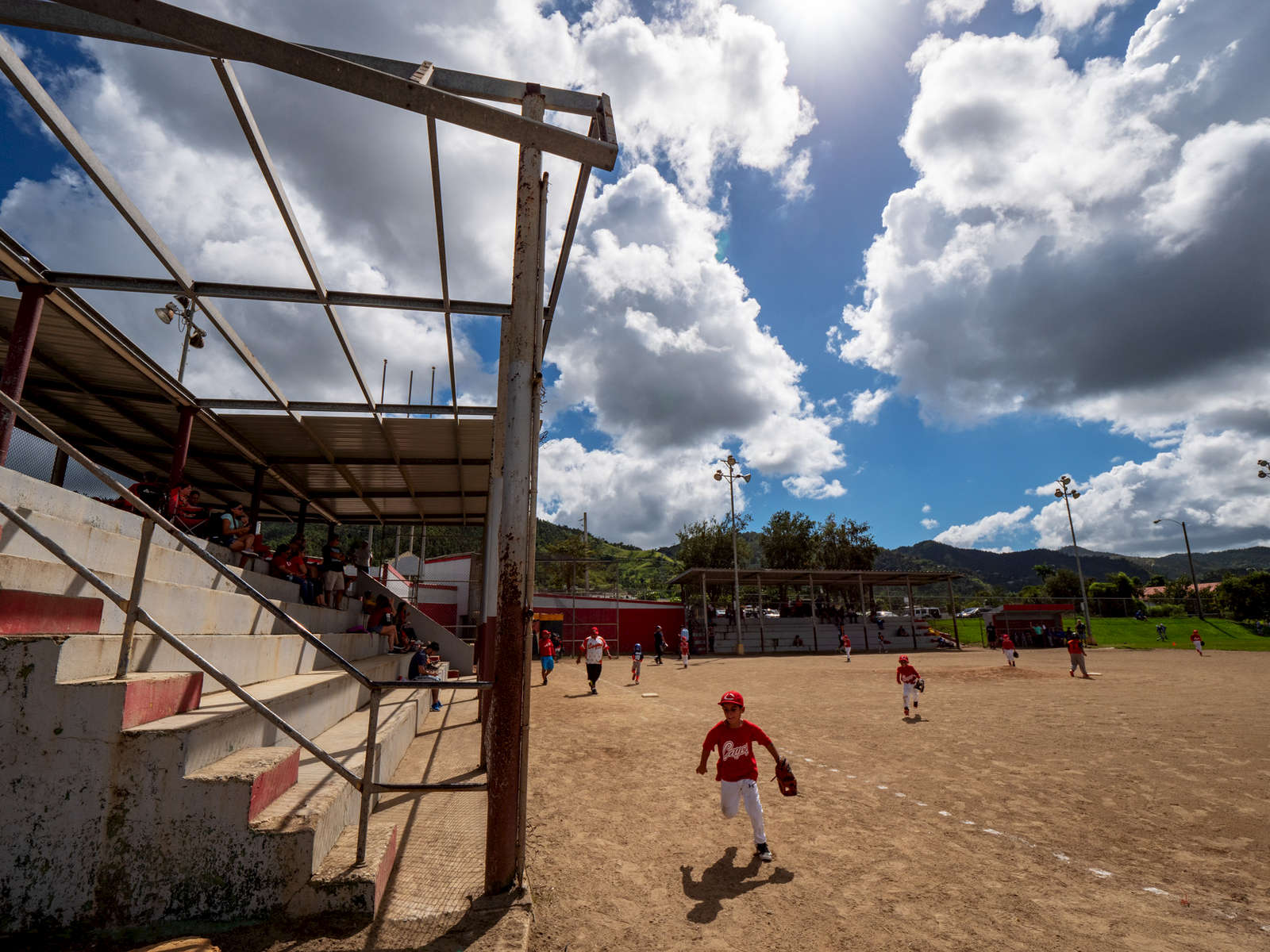 CAYEY, PUERTO RICO - NOVEMBER 10:  Fans watch children  compete in a Little League baseball game under a damaged roof caused by Hurricane Maria on November 10, 2018 in Cayey, Puerto Rico. The effort continues in Puerto Rico to remain and rebuild more than one year after the Hurricane Maria hit and devastated the island on September 20, 2017. The official number of deaths from the disaster is 2,975.
