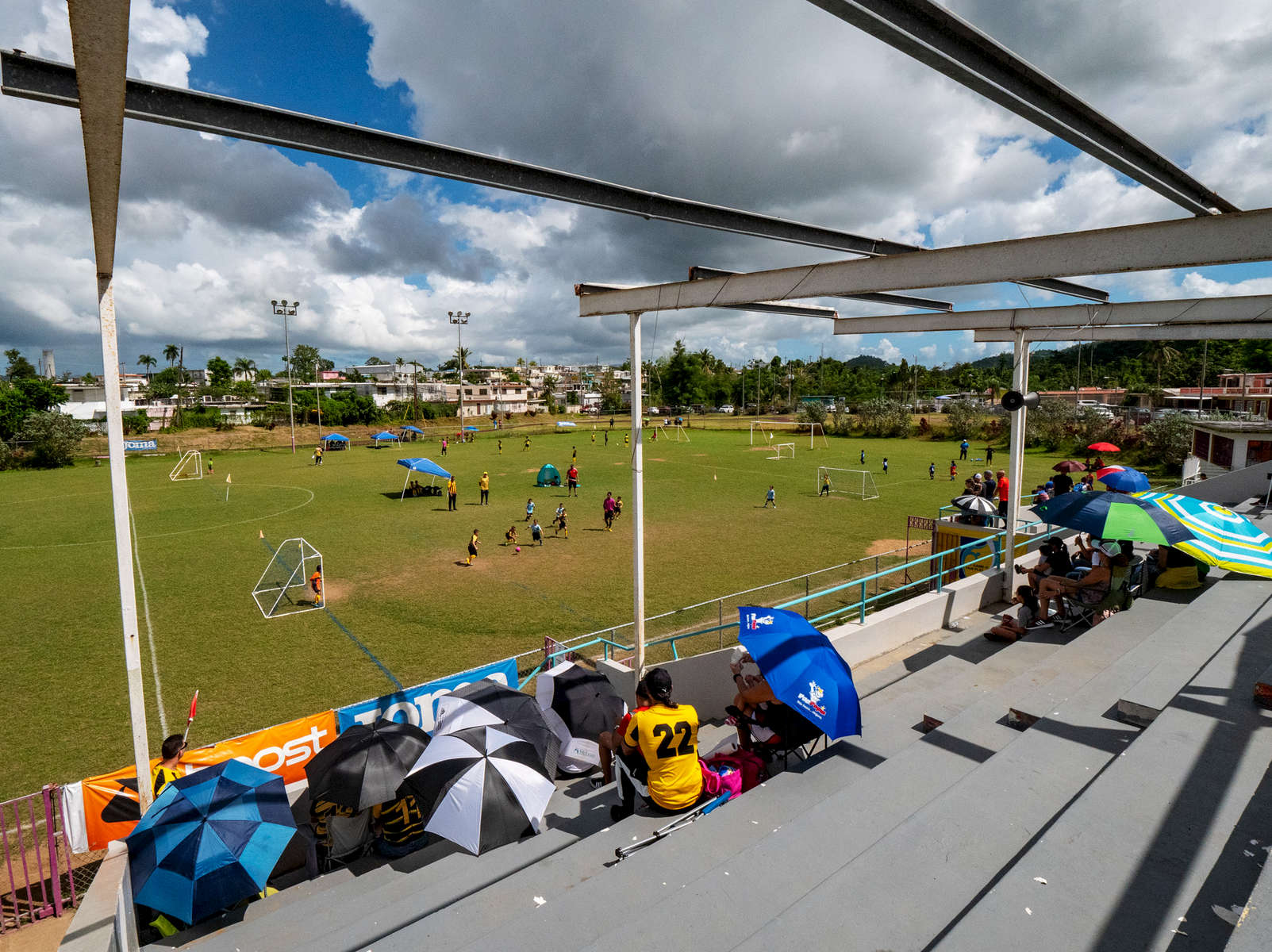CAGUAS, PUERTO RICO - NOVEMBER 10: Parents watch their kids play Little League Soccer under a damaged roof caused by Hurricane Maria.  They are using umbrellas to shield themselves from the Sun.  on November 10, 2018 in Caguas, Puerto Rico. The effort continues in Puerto Rico to remain and rebuild more than one year after the Hurricane Maria hit and devastated the island on September 20, 2017. The official number of deaths from the disaster is 2,975.