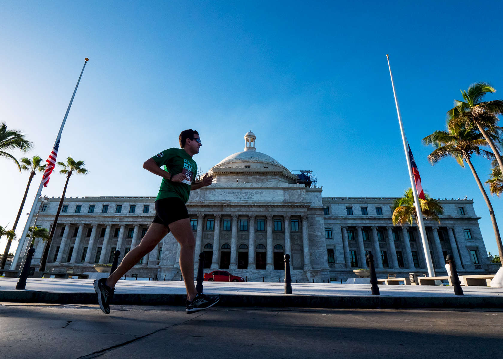 OLD SAN JUAN, PUERTO RICO - NOVEMBER 11:  An athlete competing in a 5k race runs past the Capitol Bulding on November 11, 2018 in Old San Juan, Puerto Rico. The effort continues in Puerto Rico to remain and rebuild more than one year after the Hurricane Maria hit and devastated the island on September 20, 2017. The official number of deaths from the disaster is 2,975.