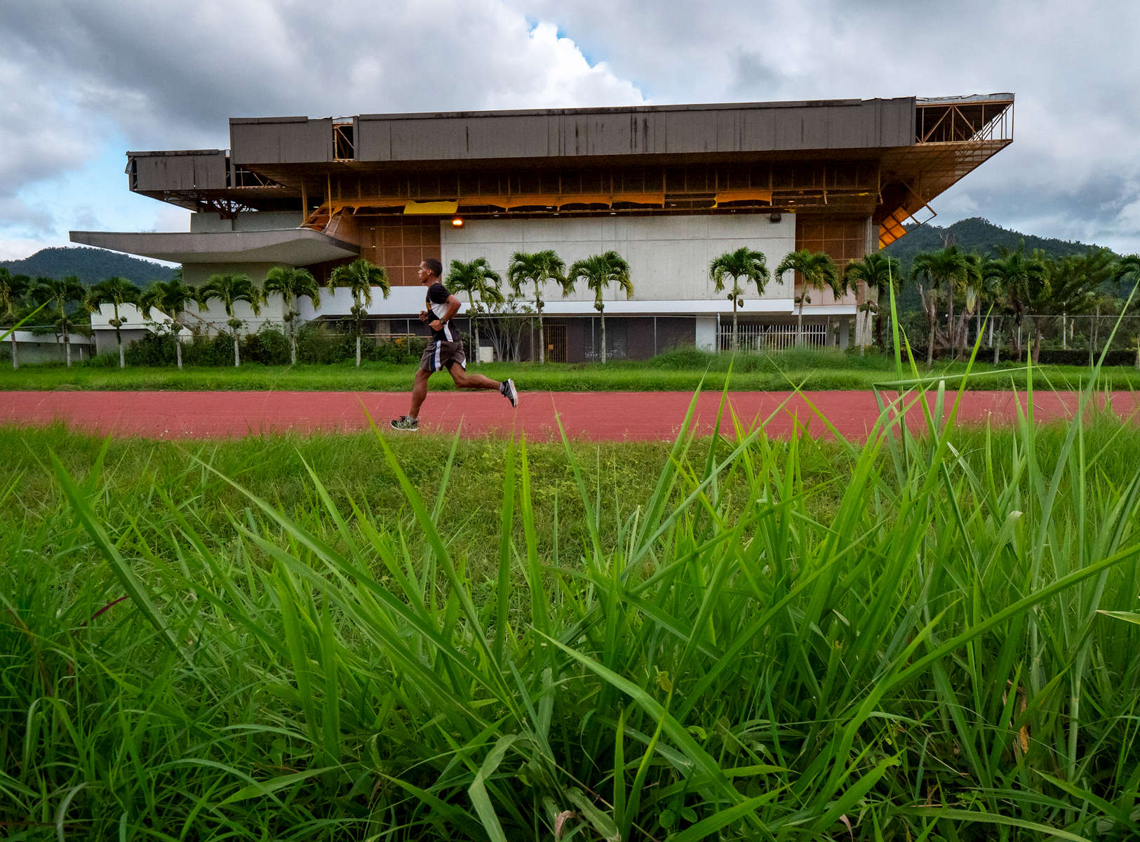 CAYEY, PUERTO RICO - NOVEMBER 10:  Juan Hernandez Gonzalez who is a student at the Cayay campus of the University of Puerto Rico runs on the University's athletics track that that had been damaged by Hurricane Maria and is now overun by uncut grass on November 10, 2018 in Cayey, Puerto Rico. The effort continues in Puerto Rico to remain and rebuild more than one year after the Hurricane Maria hit and devastated the island on September 20, 2017. The official number of deaths from the disaster is 2,975.