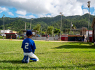 CAYEY, PUERTO RICO - NOVEMBER 10: A boy looks on during a Little League baseball game on November 10, 2018 in Cayey, Puerto Rico. The effort continues in Puerto Rico to remain and rebuild more than one year after the Hurricane Maria hit and devastated the island on September 20, 2017. The official number of deaths from the disaster is 2,975.
