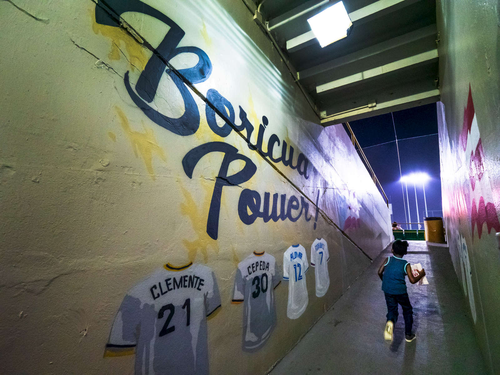 SAN JUAN, PUERTO RICO - NOVEMBER 15:  A young fan runs with a bag of popcorn into the stadium next to a hallway leading to the field with a mural on the wall with the words Boricua Power and the Jerseys of famous MLB Puerto Rican baseball players Roberto Clemente and Orlando Cepeda  during the game between the Gigantes De Carolina  against the Indios De Mayaguez during opening day of the Professional Baseball League of Puerto Rico at Hiram Bithorn Stadium on November 15, 2018 in San Juan, Puerto Rico. The effort continues in Puerto Rico to remain and rebuild more than one year after the Hurricane Maria hit and devastated the island on September 20, 2017. The official number of deaths from the disaster is 2,975.