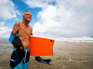 PINONES, PUERTO RICO - NOVEMBER 16:  Luis Santiago of San Juan poses for a portrait at Aviones Beach on November 16, 2018 in Pinones, Puerto Rico. He lost his right arm in a surfing accident when he crashed in a wave on the rocks when he hit the sea floor. He still rides his Boogie Board on this same beach whenever he can.  The beach flooded the town of Pinones and all the neighboring towns during Hurricane Maria.  The effort continues in Puerto Rico to remain and rebuild more than one year after the Hurricane Maria hit and devastated the island on September 20, 2017. The official number of deaths from the disaster is 2,975.