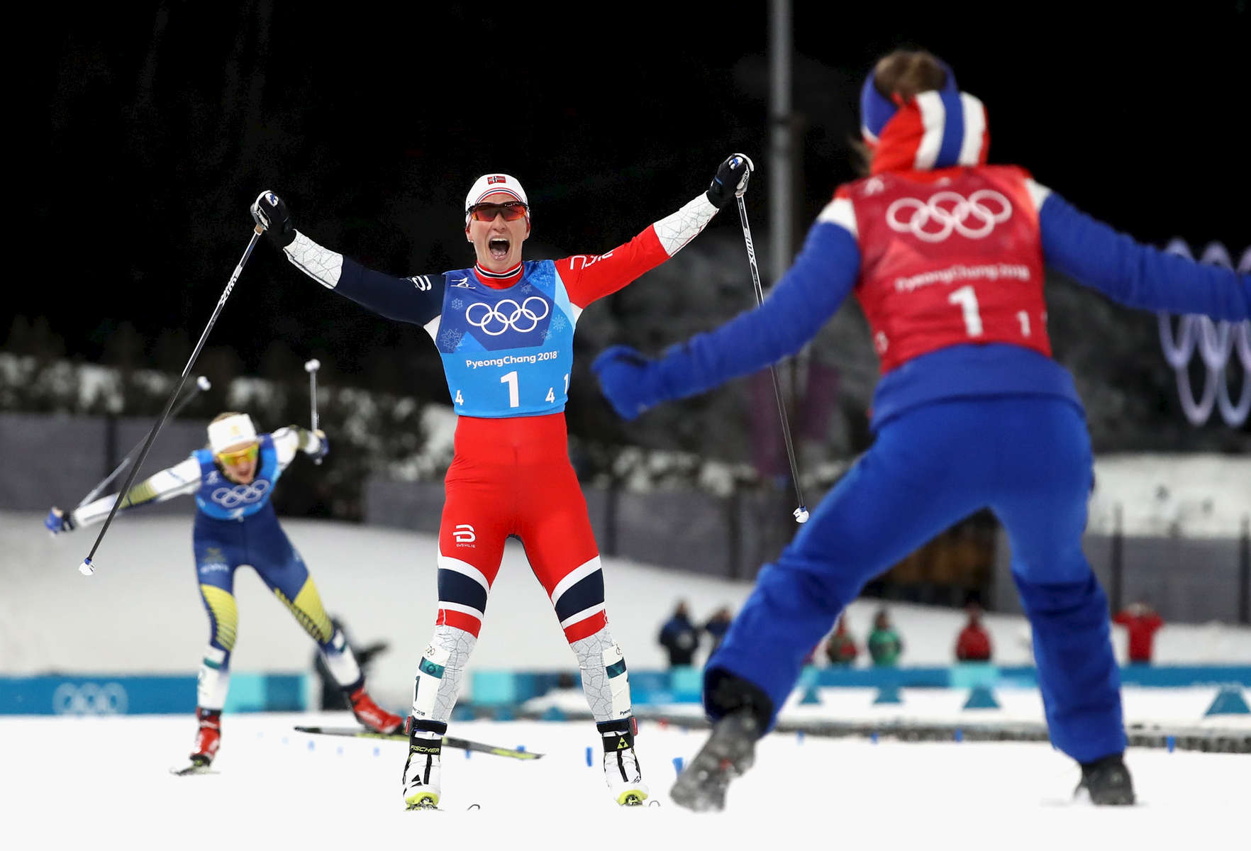 Marit Bjoergen of Norway (1-4) celebrates as she crosses the finish line to win gold with Ingvild Flugstad Oestberg of Norway (1-1) during the Ladies' 4x5km Relay on day eight of the PyeongChang 2018 Winter Olympic Games at Alpensia Cross-Country Centre on February 17, 2018 in Pyeongchang-gun, South Korea.