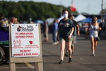 A sign is displayed promoting wearing a face mask and social distancing during NASCAR Advance Auto Series Opening Night  at Riverhead Raceway on August 01, 2020 in Riverhead, New York.  The race track had been closed due to the coronavirus COVID-19 pandemic.  More than 4,585,258 people in the United States alone have been infected with the coronavirus and at least 154,000 have died.