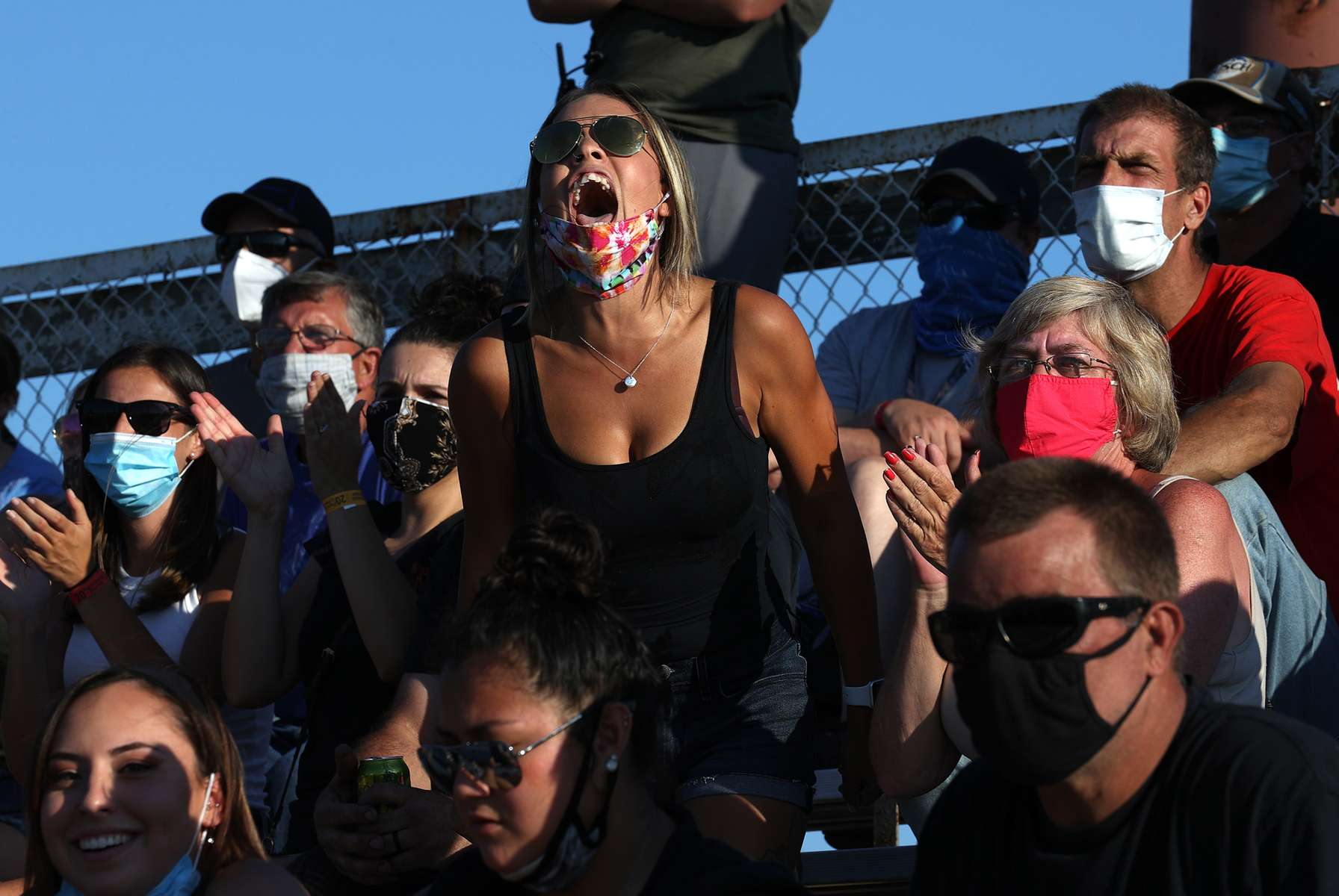 Fans cheer the cars racing around the track during NASCAR Advance Auto Series Opening Night at Riverhead Raceway on August 01, 2020 in Riverhead, New York.  The race track had been closed due to the coronavirus COVID-19 pandemic.  More than 4,585,258 people in the United States alone have been infected with the coronavirus and at least 154,000 have died.