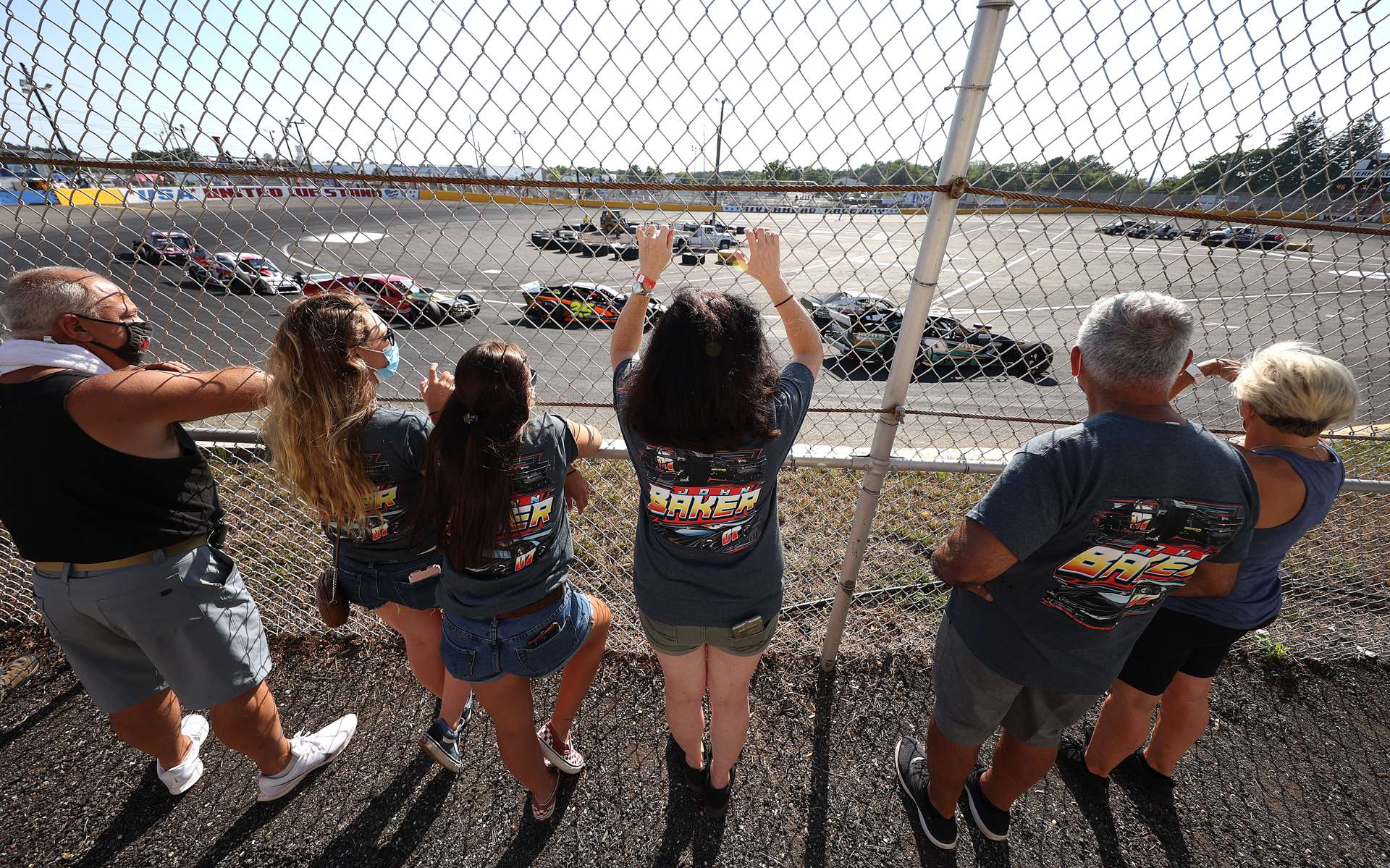 Fans watch cars racing around the track during NASCAR Advance Auto Series Opening Night at Riverhead Raceway on August 01, 2020 in Riverhead, New York.  The race track had been closed due to the coronavirus COVID-19 pandemic.  More than 4,585,258 people in the United States alone have been infected with the coronavirus and at least 154,000 have died.